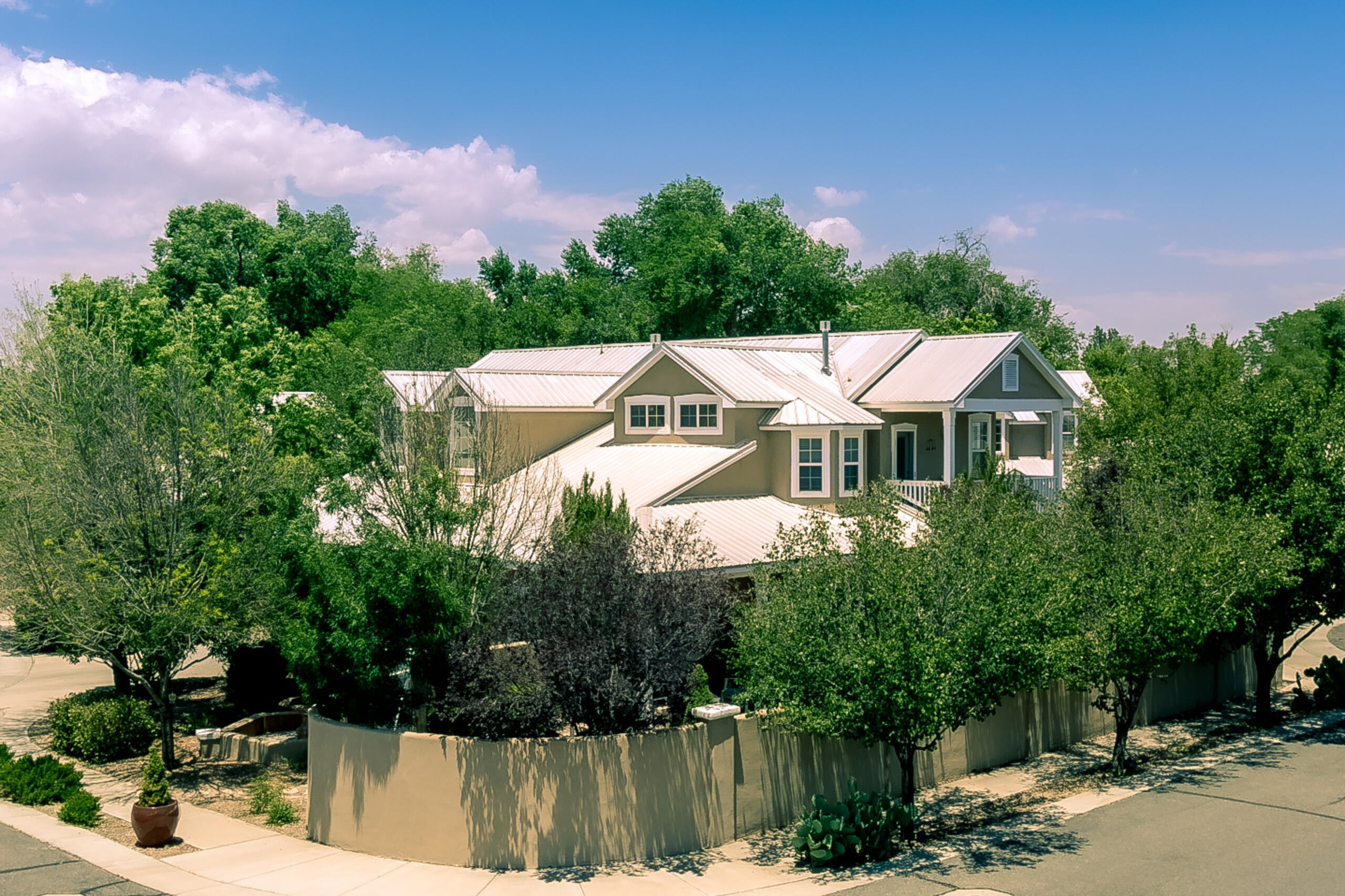 Masterfully designed former builder Model Northern NM style home nestled on a 1/4 Acre cul de sac corner lot in the gated  El Manzanito Estates North Valley Albuquerque. Loaded w/builders options & upgrades incl Soaring beam ceilings in main living area, Diamond plaster FP between living rm & kitchen. Brazilian Teak hardwood  floors. Spacious kitchen features Hickory Cabinets, granite counter tops, built in stainless steel gas cooktop, separate convection oven, pantry, island & breakfast bar.  Gracious owners suite features 2-way diamond plaster FP, large walk-in shower, garden tub, dbl sinks, 2 closets & private deck w/views. Relaxing east facing covered flagstone patio w/water features & mature landscaping, Spacious 2nd & 3rd bedroom w/Jack & Jill bathroom. 2nd owners suite downstairs.