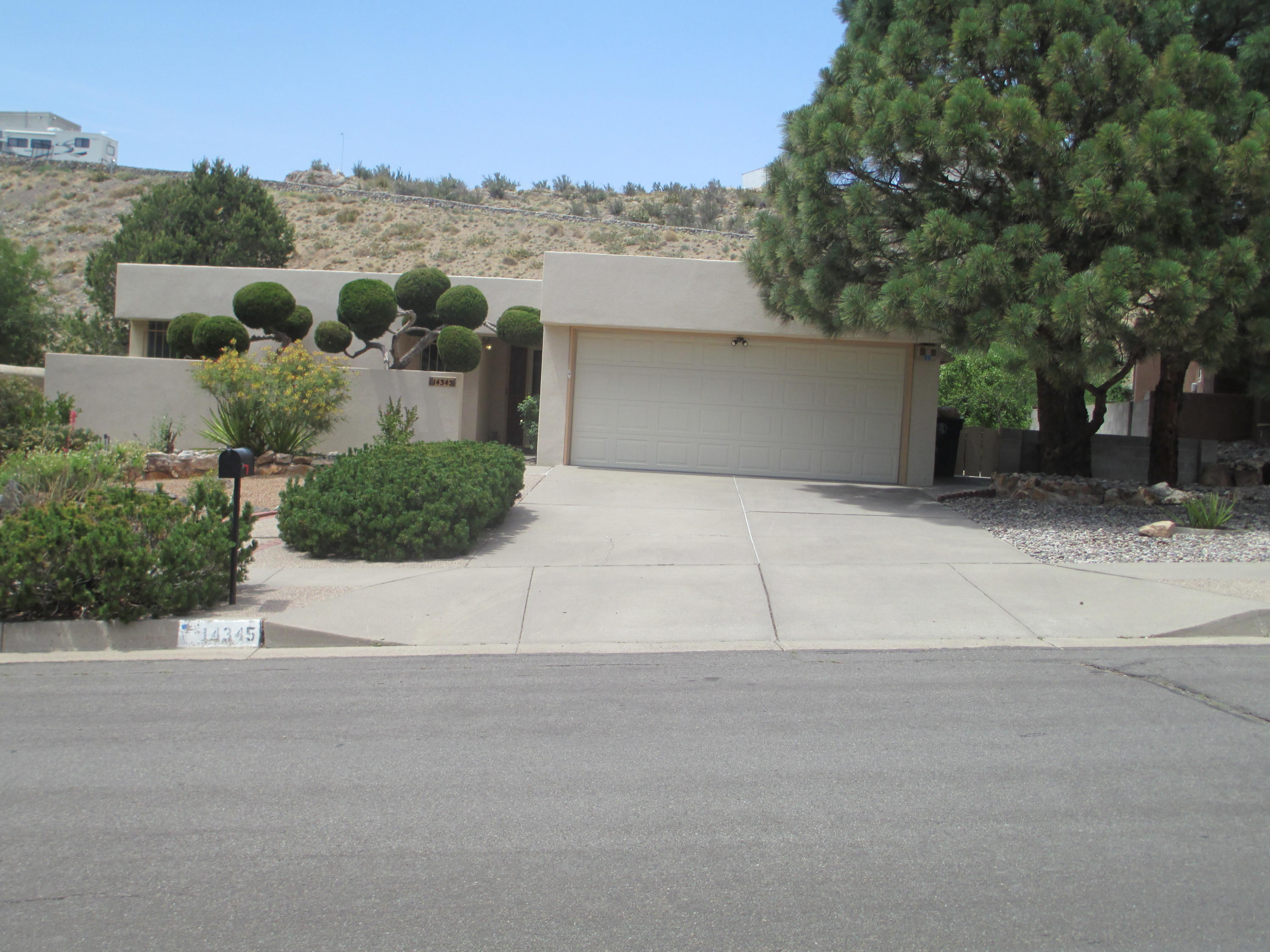 Custom Home at foot of Mountains.  3 Bedrooms 2 full bathrooms. Sunken Living room w/skylights, ceiling fan, dry bar, raised ceilings and Kiva Fireplace. Formal Dining room, Kitchen with Breakfast area, Bay window and tile floors. Covered front entry off walled Courtyard. Lg. Screened in back patio w/french doors from the living room and master BR. Skylight, 3 closets, double sinks, sunken garden tub and separate shower in Master Bath. Sunken Master Bedroom w/ kiva fireplace too. Recessed lighting, Security Wrought w/safety releases. Additional 290 sq ft. heated workshop/garage in back. Beautifully landscaped F & B yards w/timed sprinklers. Lg. 2 car garage. Rolled roofing, thermal double pane windows. Block wall in back. Not many homes come available in this neighborhood. Come see it soon