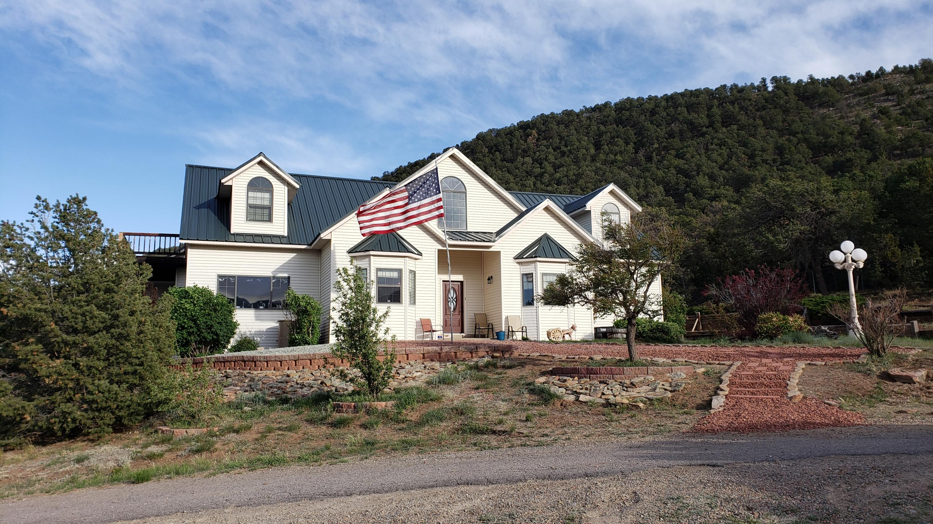 Stunning Panoramic Mountain views, fenced 3 acres with private backyard landscaped patio & 2.6 additional acreage (5.6 acres total), feels like you own your own mountain with access to hiking & riding trails. Minutes to dining & shopping close to ABQ. Incredible open floor plan, includes a beautiful master suite, three other large bedrooms, & office. Wonderful marble windowsills. Freshly painted rooms &updated lifetime flooring (redwood/waterproof}  Toilets & sink fixtures replaced in 2021. Cost saving LED lighting. Easy cleaning Harmon Pellet stove sized to heat the home. Modern water system includes a well & rainwater harvest (7100 gallon) making this East MTN home drought resistant. Spacious 4 stall horse barn, 3 car garage, fruit trees & shed.