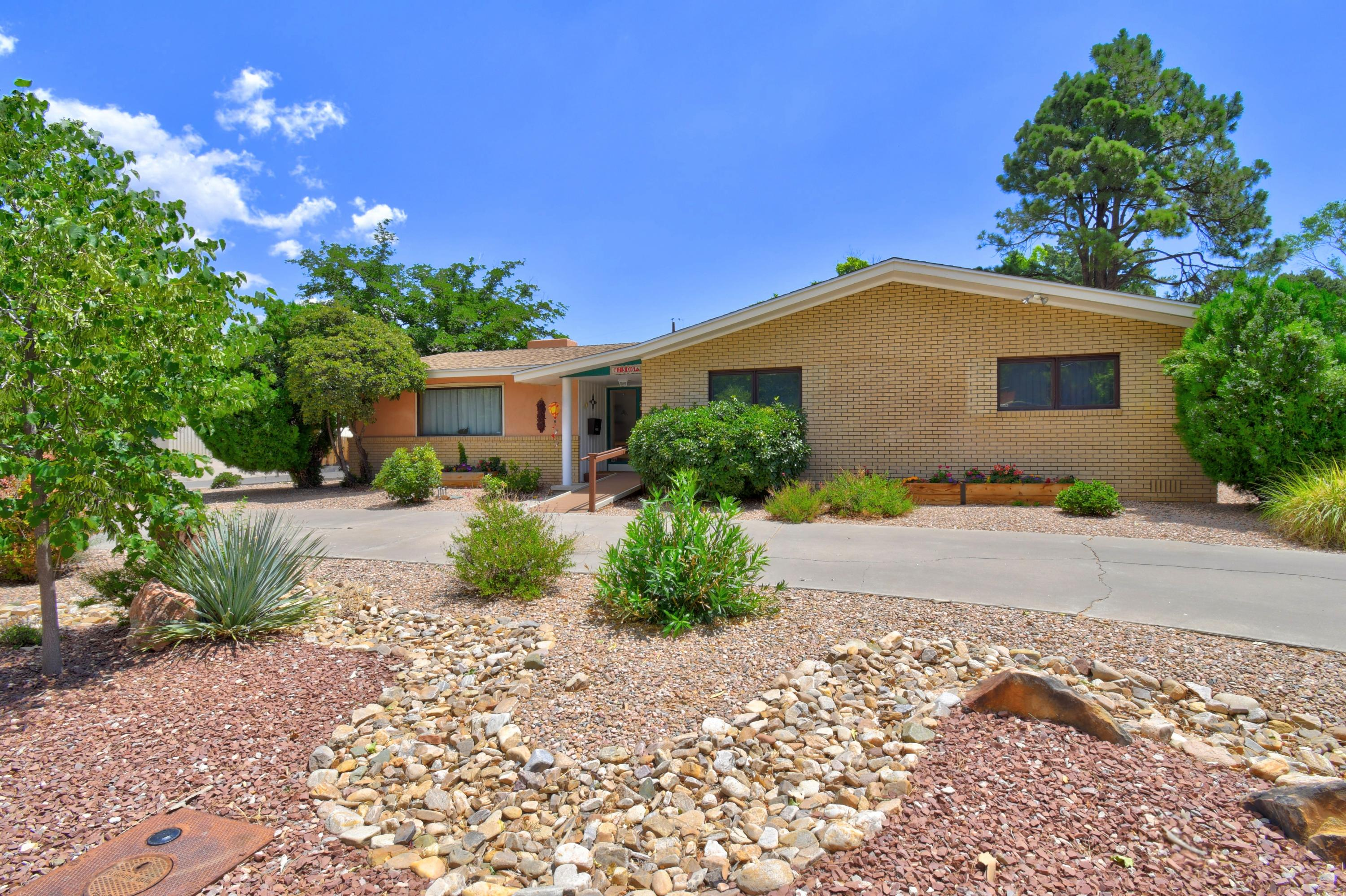 Sensational single level custom home on large corner  lot across from UNM golf course (1/4 acre). Loaded with character & charm, spacious floorplan with two large living rooms, tons of natural light, cozy fireplace, beautiful landscaping front & back, hardwood floors throughout, circular driveway on one side & 2 car driveway on the other side. Ideally located in Vista Larga with plenty of space to enjoy both inside & outside. Lovingly cared for & you can move in with peace of mind as all mechanics have been replaced. Newer roof, heating & refrigerated air cooling system, water heater, sprinkler & drip system, electrical in 2018.  Newer windows. Doors have been widened.  Master bathroom has been updated with a roll-in shower. 2 car garage is oversized with vaulted ceiling.