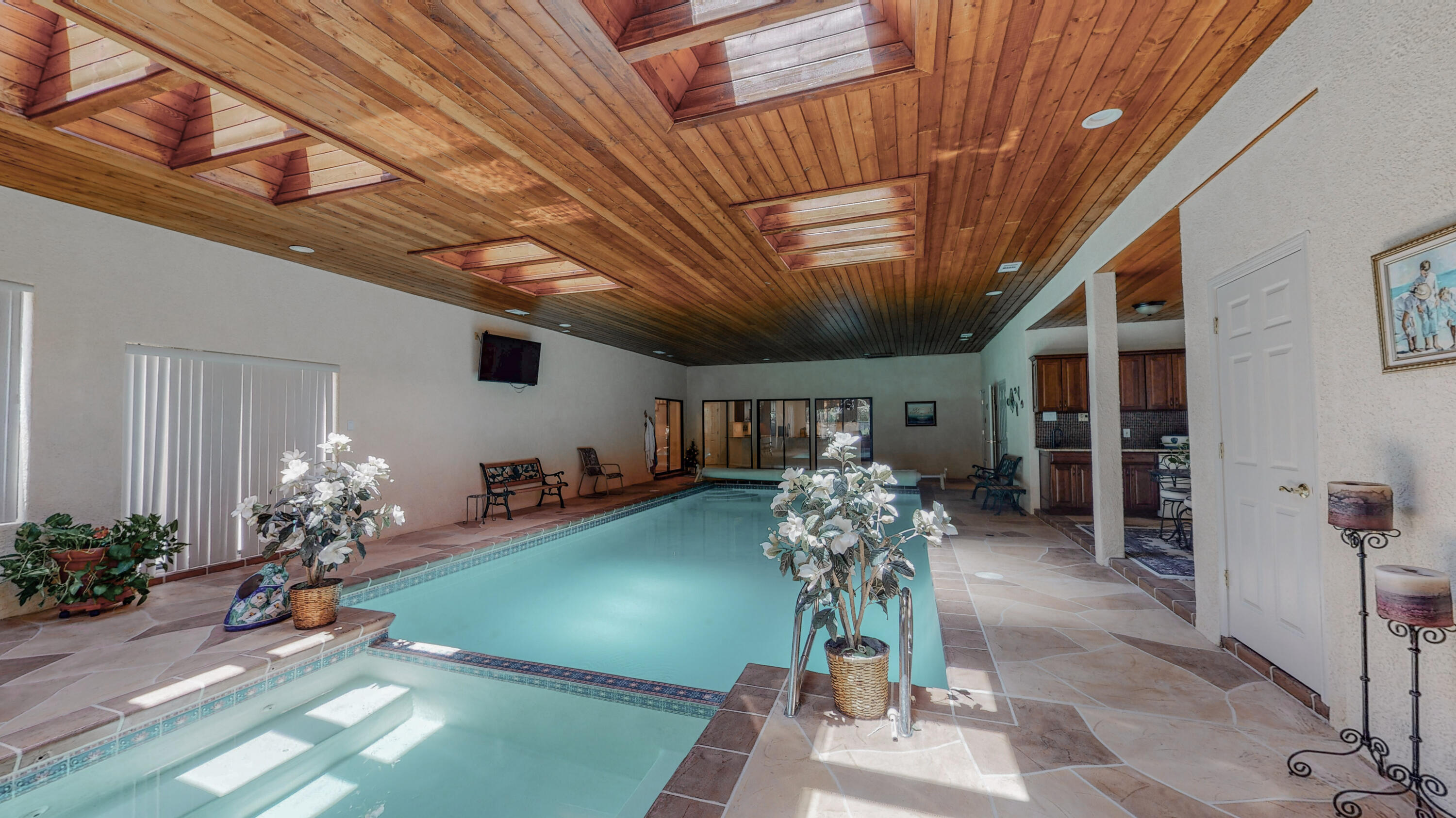 Impeccable 5-bed, 4-bath, 4-car garage home bursting with upgrades and amenities, from the enormous indoor pool and hot tub with changing room, bathroom, and wet bar with fridge, to the updated kitchen featuring a huge granite peninsula with solid wood, dovetailed, soft close cabinetry, chef-grade appliances, and full size pantry, to the large living room filled with natural light from the massive windows, complete with quartz fireplace hearth, to the spacious owner suite with private balcony looking over the city, while the jetted tub, steam shower, two large walk-ins, and double sinks round out the en-suite. Don't miss another deck with mountain views, TPO roof, recirculating hot water, hands-free faucets, LED and nightlight lighting, and so much more, nestled at the base of the Sandias.