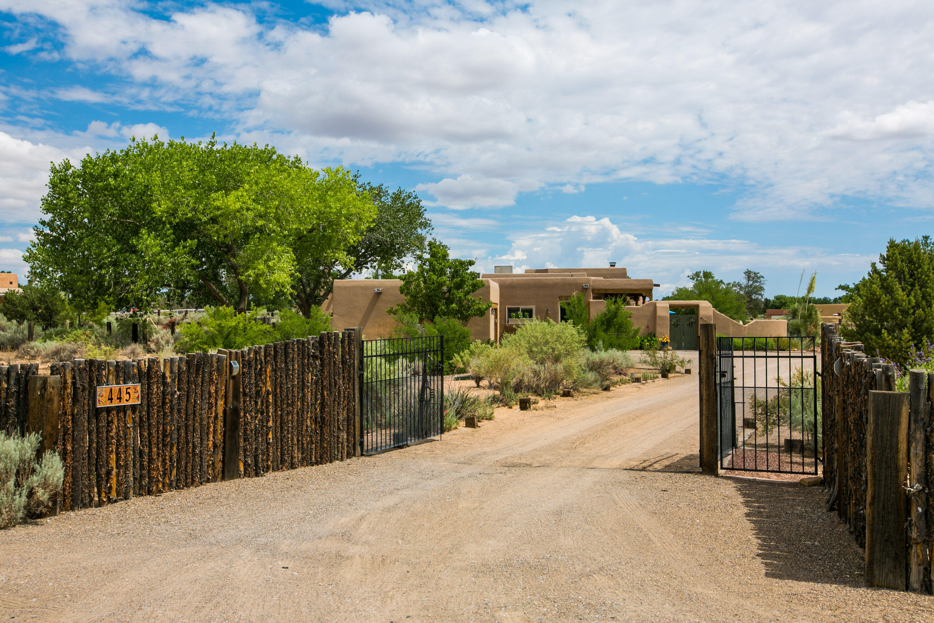 Take a look at this great Corrales property! The entire lot is fully fenced and gated for privacy. Upon entering, you will be greeted by a lovely lush courtyard with beautiful plantings, a covered portal, and spectacular views of the Sandia Mountains. The home was designed to take advantage of the views from the living area, the kitchen and breakfast nook, and the huge home office! Charming Southwestern design features include exposed adobe, a Kiva fireplace, wood beamed ceilings with Vigas, Saltillo tile, Talavera tile imported from Mexico, and handcrafted doors throughout. Built in bookcases in the great room, and a built in desk in the home office offer tons of storage. The Village of Corrales offers a rare opportunity for country living minutes from the city amenities!