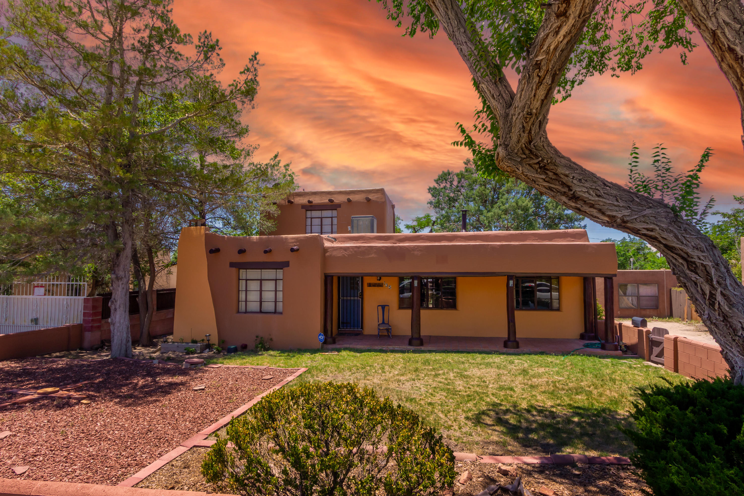 Charming pueblo-style home. Beautiful brick and hardwood floors are married to timbered ceilings, custom wood doors with original rustic hardware and THREE custom Kiva fireplaces. There's a cozy dining area, a sun room and an open kitchen. Brick walls frame the large front and back yards, both well-maintained with mature trees and shrubs. Enjoy Sandia mountain views from the upper bedroom or a quiet moment the very Private backyard. There's also a covered porch off of the two car garage and a place to keep chickens. Close to markets, restaurants and rapid transit.