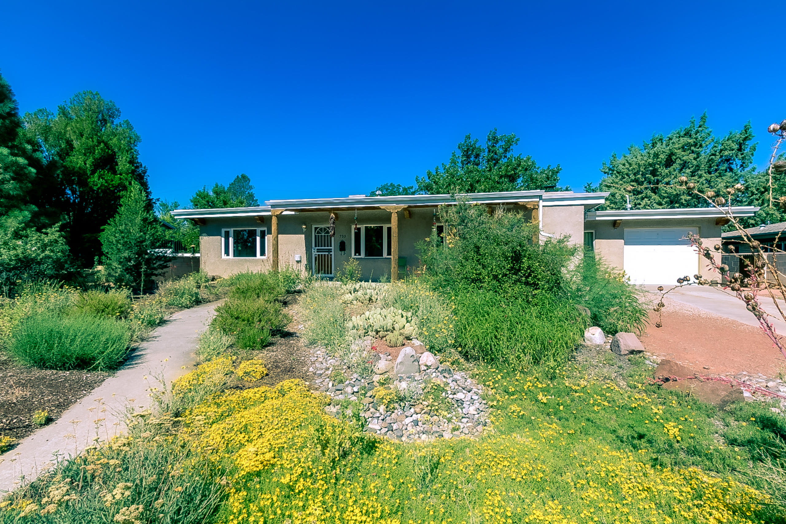 This eminently livable UNM Area casa evokes a blend of Mid-Century comfort & SW charm. The sunlit 1950 sq ft residence boasts 3 bdrms 2 full baths & 1 car garage on landscaped 0.23 acre lot. 2015 kitchen renovation includes custom hickory cabs, granite counters, stainless appliances/hanging vent hood & added interior space w/ pantry & laundry area. Kitchen open to living room. Sizable den w/ fireplace at opposite side of kitchen. Large main bdrm w/ French doors, walk-in closet & en suite w/ jetted tub & shower. 2 add'l bdrms separate from the main & divided by the full hallway restroom. Refinished oak hardwood floors. Thermal windows. Private backyard boasts a huge contemporary metal pergola w/ diagonal slats, hot tub, lawn & mature fruit trees. Close to Nob Hill, UNM & mid-city amenities.