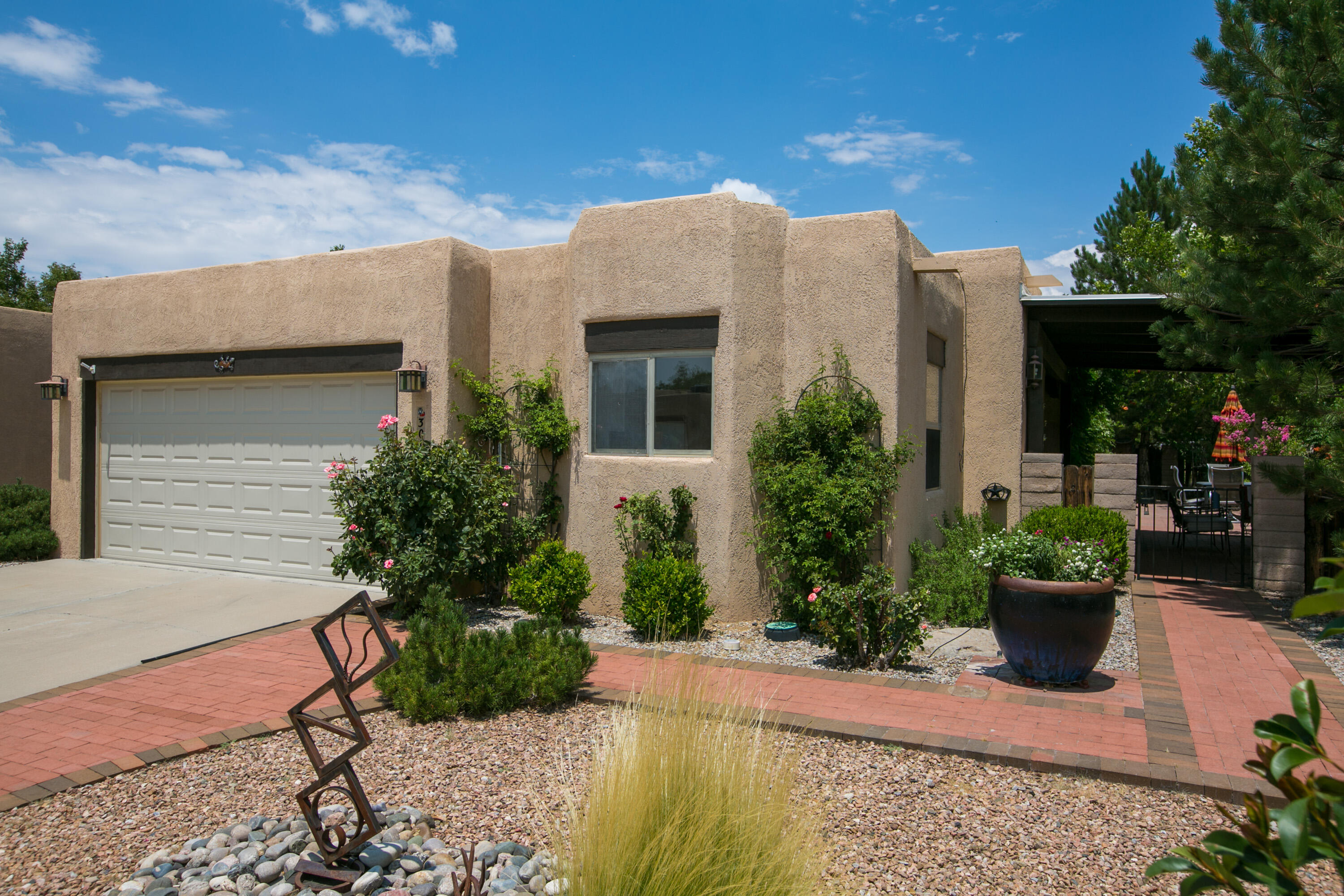 Best location in an already wonderful community, this charming one level home boasts views of the private walking space, and easy access to the acequia for recreation. Feel like you have a huge, lush yard with the ease of an easy care patio. The house has a flexible floorplan one of the three bedrooms currently configured as an office.  No closet but can easily be used as a bedroom. Lots of updates including kitchen cabinets and more. Two fireplaces, wood ceilings and more make this home a true north valley gem.