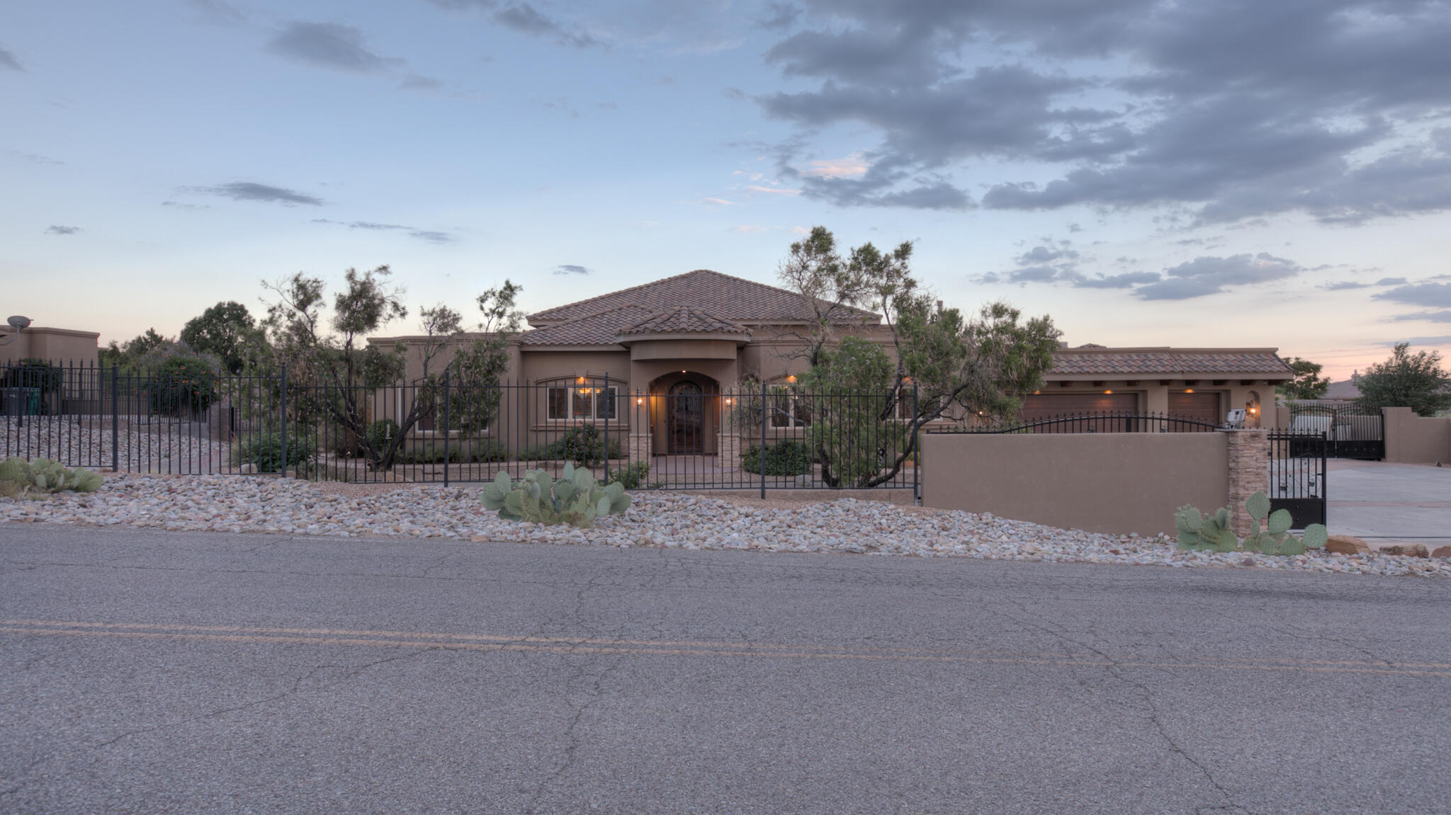 Welcome home to this exquisite estate in North Albuquerque Acres.  Nestled on a large lot with its own private guest house, this nearly 5,000 sq foot property has it all.  Wolf and sub zero appliances, stunning hand carved woodwork throughout, vaulted ceilings, beautiful beams, large open floor plan, two separate patios, storage galore, and custom lighting both inside and outside the house. Large bedrooms have walk in closets and attached en-suit private bathrooms. Primary bedroom is separate from the other rooms, has a door out to the back patio, two separate closets and sinks/vanities, huge shower with stained glass and custom tile work.  Enjoy a perfect backyard that is fully landscaped and complete with a hot tub, pool, huge patio, deck and kitchen perfect for entertaining, fruit trees