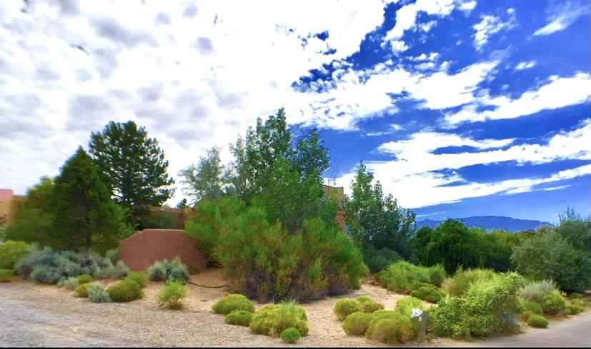 Head on views of Mts. & City! This fabulous home was built & designed as the est. ''Yours Truly B & B . Hidden behind mature landscaping for privacy, yet located conveniently for access to Albuquerque, Rio Rancho, & 10 minutes from shopping. Open & light floorplan, beams, Vegas, brick floors, 5 kiva fireplaces. Spacious great-room, formal dining, chefs kitchen w/island, primary bedroom, plus 3 ensuite bedrooms, a 4rd ensuite  w/ separate entry, all on the main floor, plus a two extra long garage w/storage, & service room. Upstairs boasts a separate 5th BR w/living, FP, tile floors, deck, & even more amazing panorama views of city & mountains. Magical outdoor expansive patio's, portal, kiva FP, make this home a pleasure to entertain both inside & out. Just imagine, it could be yours!