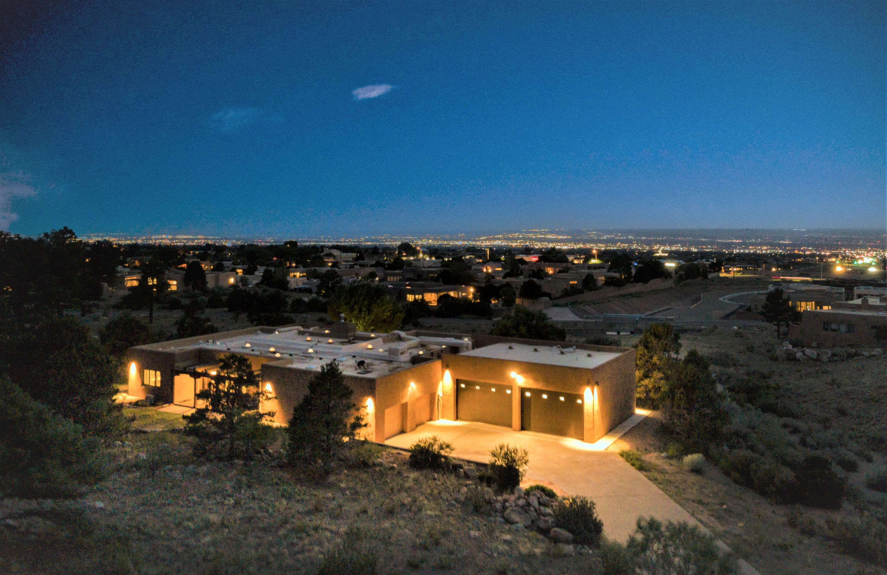 Gorgeous 1 level custom home, built by Jack Wirtz, in SANDIA HEIGHTS!  Located on  a 1 acre lot with city and mountain views, this property features 3 or 4 bedrooms, 3 bathrooms, a gorgeous remodeled kitchen (in 2017 that includes quartz countertops, red oak cabinets, subzero refrigerator/freezer, and more), and a 6 car garage (that totals approximately 2,000 square feet... the 4 car garage is wired for 2 mini-splits. The primary bedroom is large (as all of the bedrooms are) with a spa-like bath and shower (2017).  Energy efficient 18'' block concrete filled exterior walls, solatube lighting throughout the house (21 installed), antique stained glass external and internal doors, .  A must see !!