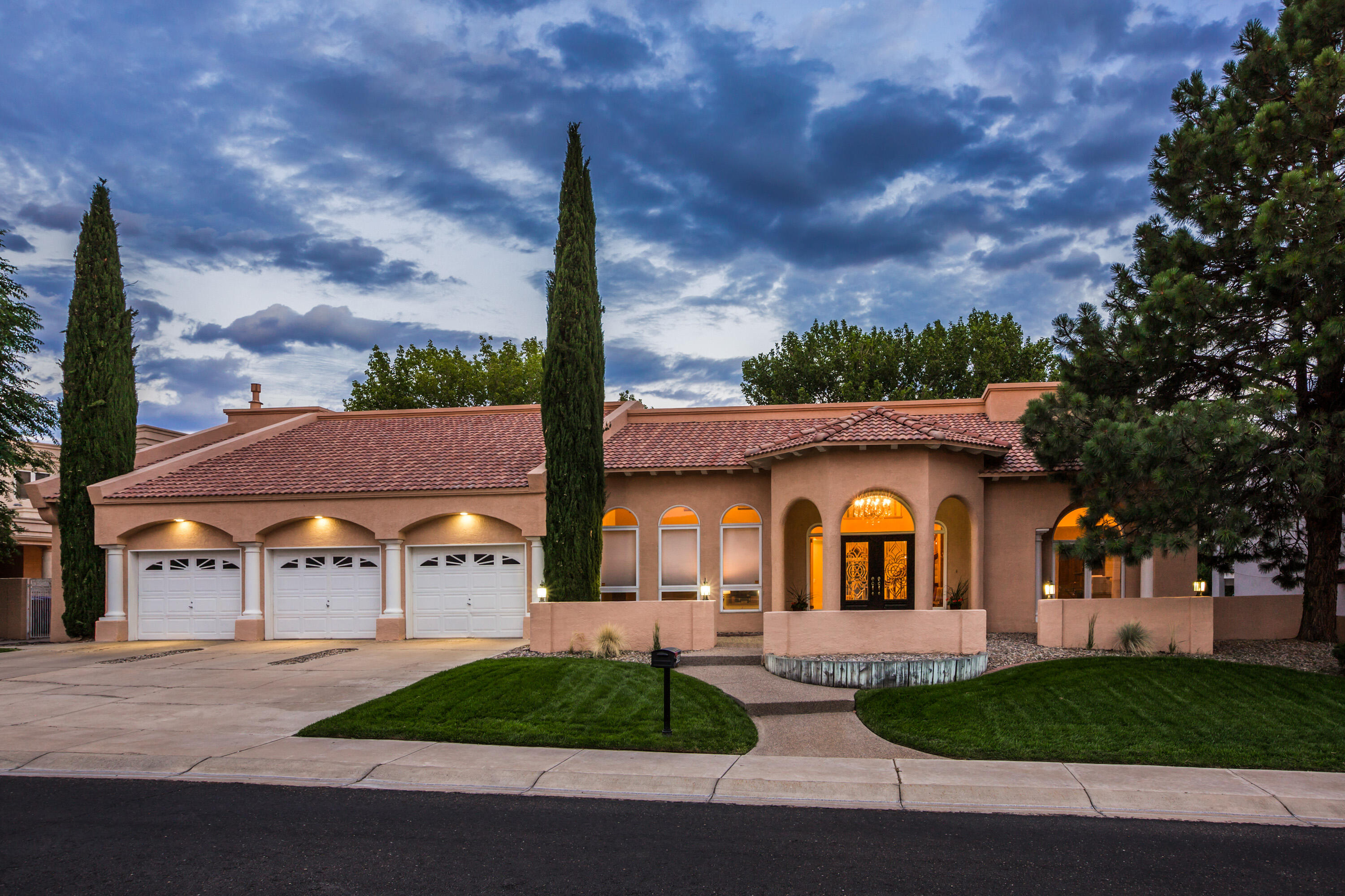 Incredible find in Tanoan, Albuquerque's only 24/7 Guard Gated Golf Course and Country Club Community. This custom home will take your breath away when you enter the grand foyer with a beautiful sweeping staircase. There are both formal and informal living and dining areas, and the great room features a beautiful fireplace, a sunken bar, and beautiful arched windows overlooking the lush backyard and the golf course. The large kitchen features a walk in pantry, rich granite, a breakfast nook and access to the outdoor covered patio. There are 2 bedrooms on the main level, and 2 bedrooms upstairs in addition to the primary suite and a loft. The backyard is beautifully landscaped and offers golf course and mountain views. Oversized garage holds 3 cars and a workshop, or golf cart parking!