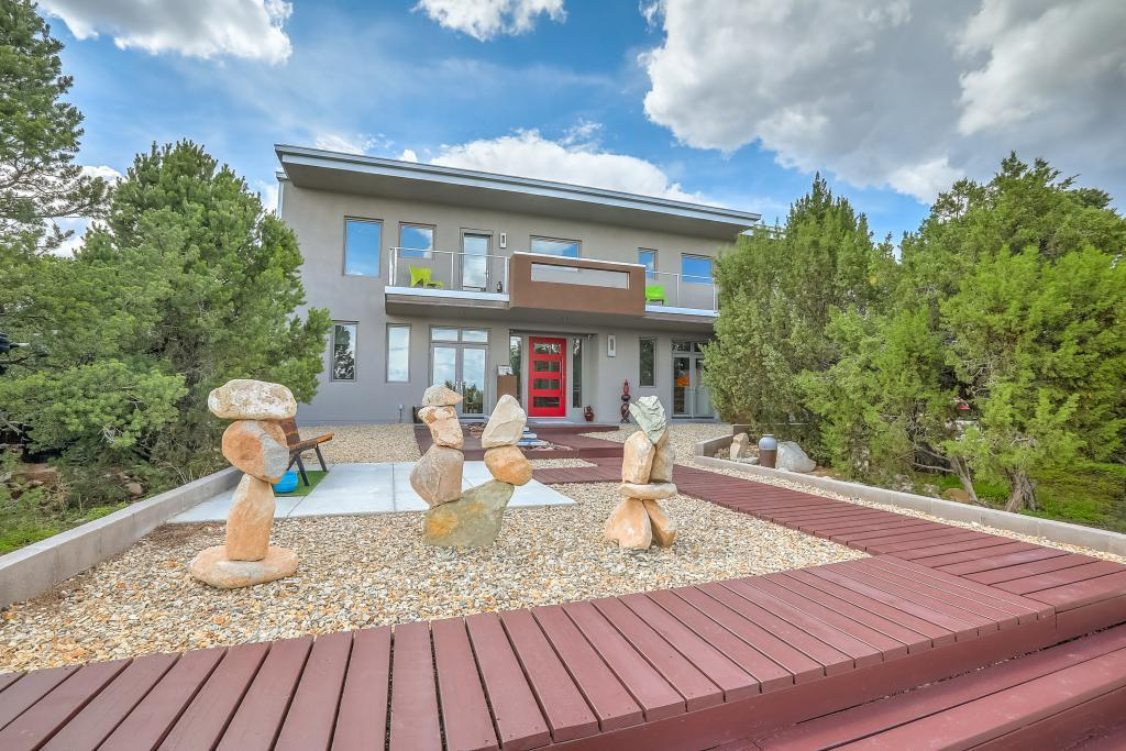 Perhaps the most beautiful home in the East Mountains! This modern, open ''NY loft'' is in the prestigious gated Tierra Encantada community. Minutes North of Edgewood, 30 min to ABQ, 45 min to Santa Fe (via Hwy 14). 4 acres cradled in trees w/ 360 views. 5.3 Kw Solar system w/ 5k gal of rainwater catchment and whole-house water filter system. Over 630 sqft of outdoor living space and a screened patio with a 15 ft folding door to bring the outdoors in. Kitchen has 13ft antique Texas bar, 3-car oversized garage, exposed metal beams, 22-ft ceilings, walls of windows, 26ft of European kitchen cabinets, light fiber internet up to 1 Gig, wired for surround sound, Passive House concept: radiant heating, Big Ass fan, powered shades, foam wrapped exterior. Your cool, quiet oasis in the mtns!