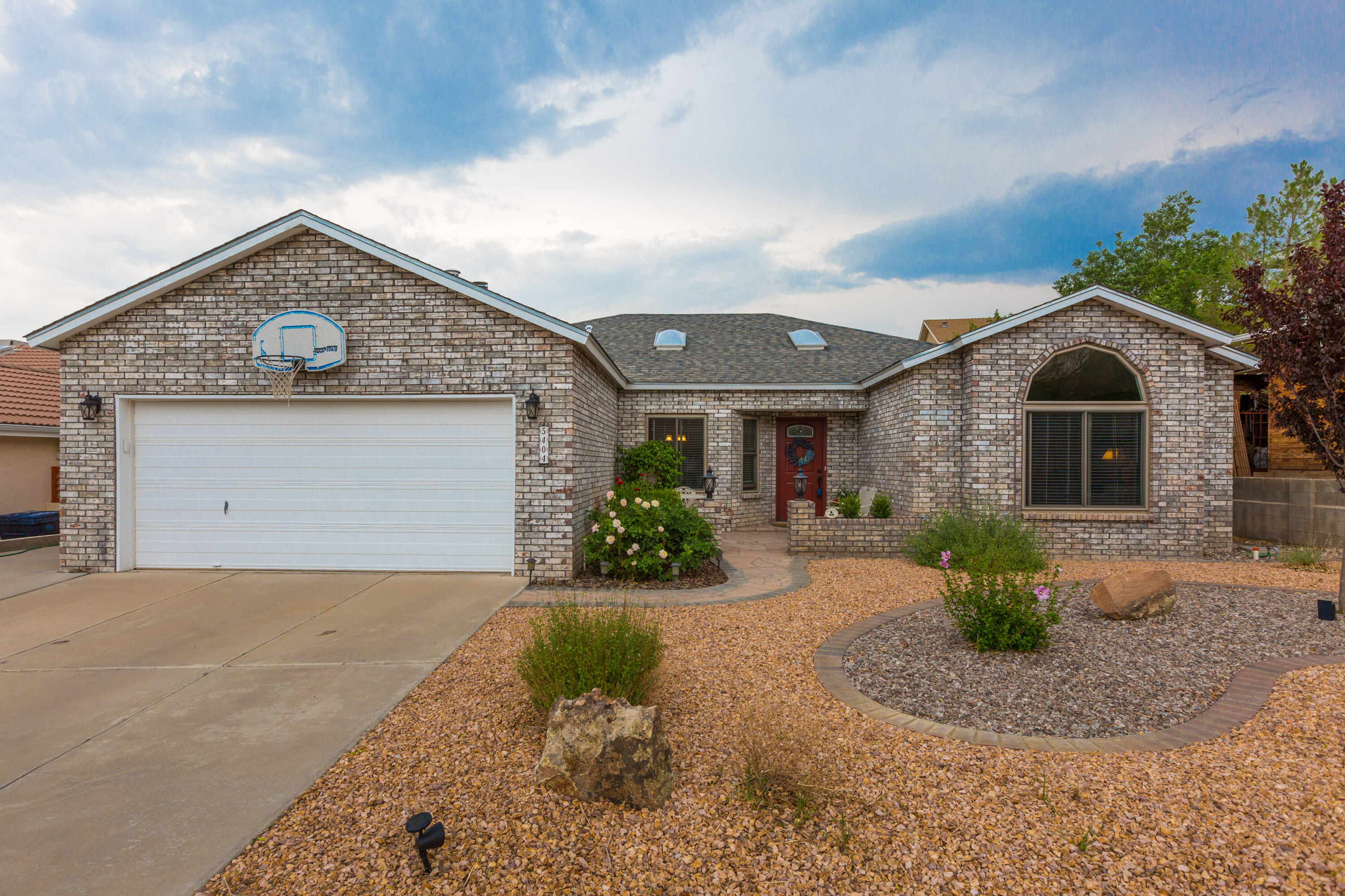 Enjoy this Custom built home, below the Petroglyph escarpment!  A 4 bedroom, single level, updated gem in an established quiet neighborhood.  The owners have meticulously updated all of the windows, (HEE) doors, flooring (tile throughout), and just look at the beautiful sunroom! 2 fireplaces, a jet tub, and oversized owners suite to rest your weary body.  A nice flowing kitchen, separate laundry room, dinette and a more formal dining area.  The front is fully landscaped and the back has been made completely ready for you to build your dream yard!Double sinks in both baths give you room for kids or guests. The 2 car garage with work bench and shelving will help you organize and keep your autos out of the weather. Come and see this one before it gets away!