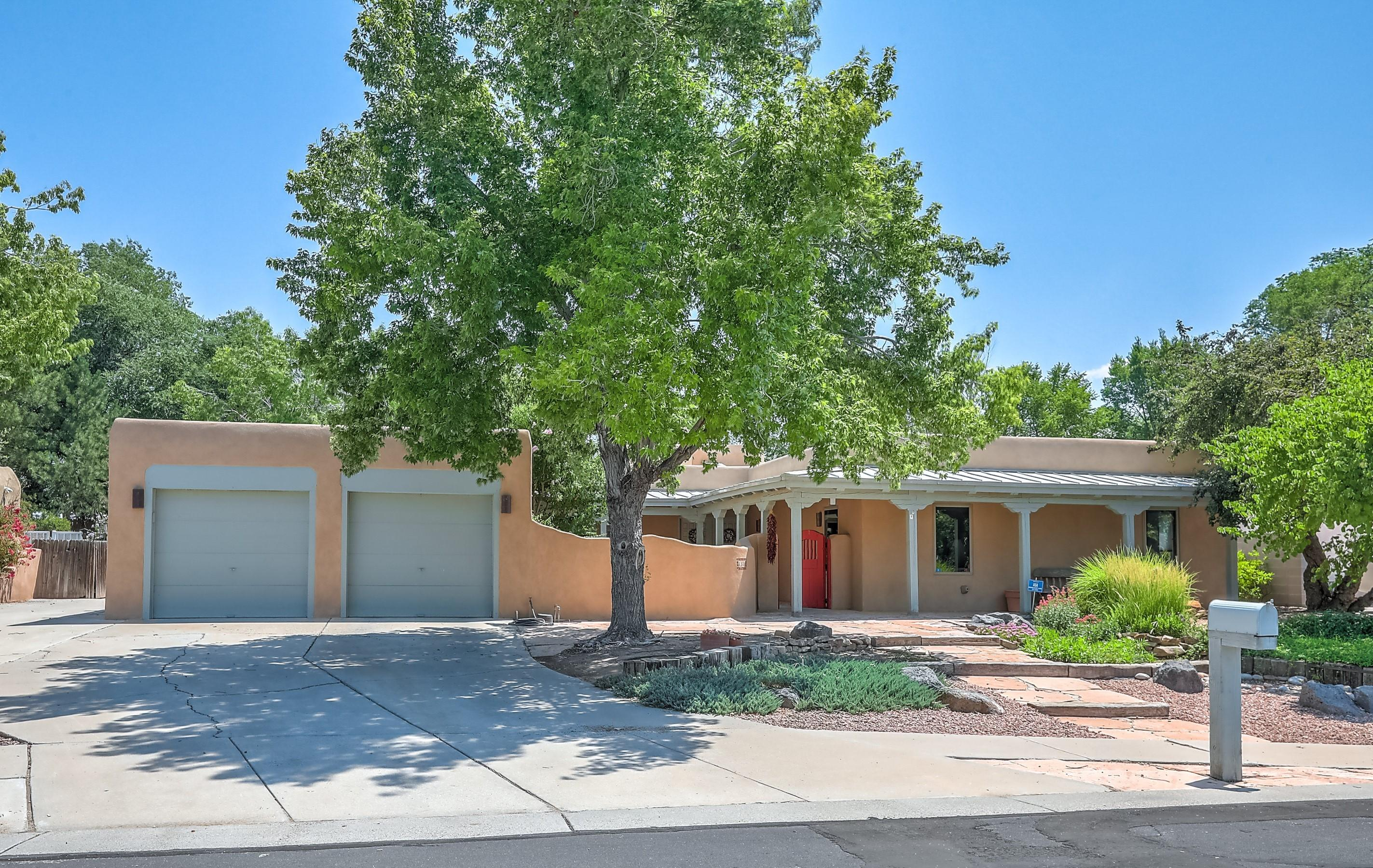 Lush property located in the desirable North Valley neighborhood of Matthew Meadow!  Much beloved pueblo style home of local artist includes an attached studio. Buyers will fall in love with the park like setting, brimming with color from flowers, trees and greenery.  Courtyard entry with stone walkway and open beam porch with corbels. Double doors open to light & bright floorplan with charming accents throughout, including tile & brick floors, skylights, & kiva fireplace. Modern kitchen with Stainless Steel appliances, plenty of cabinets, a large picture window looking to the garden and a pass-through to the formal dining room. Generous owner's suite with large custom walk-in closet, dual sink vanity, and water closet. Office with 3/4 bath could double as excellent guest quarters. (more)