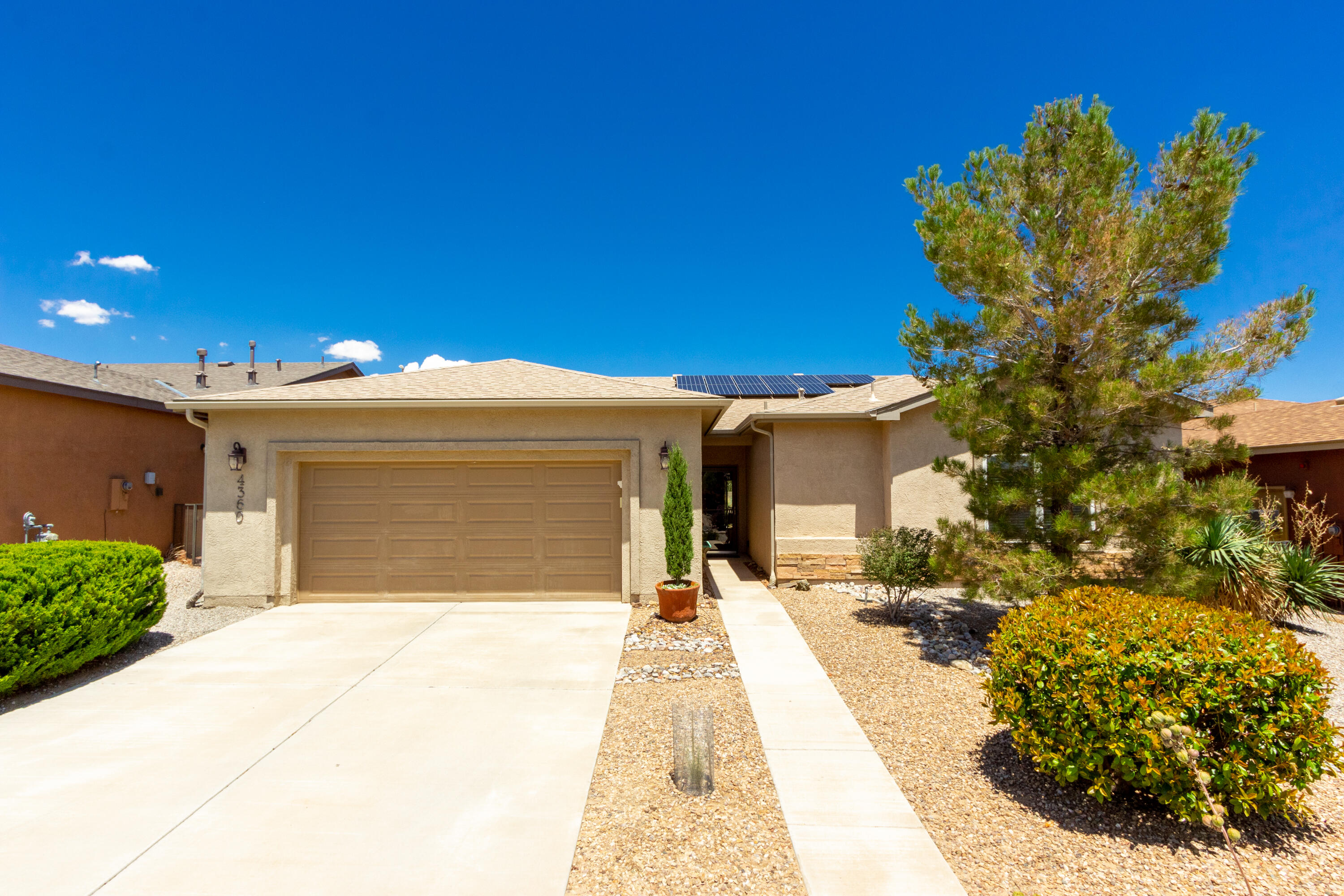 What a great location close to the clubhouse & other amenities for this wonderful home! With mature landscaping (the back yard is absolutely gorgeous!!), window coverings, upgrades & owned solar (super low electric bill) why wait to build? This spacious 1949 sq. ft. plan (Taos floorplan) is a split plan w/HUGE bedrooms....all 3 of them! The 2-car garage is oversized as well. Master bath cabs are so SW tastefully done & gorgeous mirror above.  Fireplace, pendant lights over the hi-bar, added can lights, walk-in showers in both baths, ceiling fans in all rooms, Murphy Bed, window coverings, and the fully landscaped LUSH back yard are all conveniently there to save you work & $$.  So lovingly maintained...it looks like new! So very affordably priced, especially considering electric savings!!