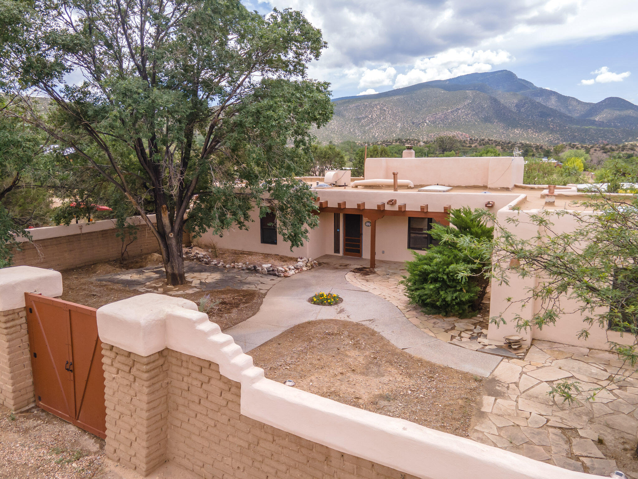 Beautifully renovated home nestled in quiet Placitas. All upgrades are under 2 years old. Bright floodlights illuminate the property which is enclosed by TALL privacy walls. Custom gates which match the garage doors. Walk in the front door to find that the entrance now opens to a light and airy kitchen. The soaring ceiling and picture window make the living room seem to go on and on giving you the feeling of being right in the Sandia Mountains. The attached greenhouse can be home to your year round garden. Relax in here protected from the elements or on the patio next to the fireplace and trickling fountain. The refurbished garage makes it great for an art studio or a man/woman cave to escape to. VA assumable loan is also an available financing.