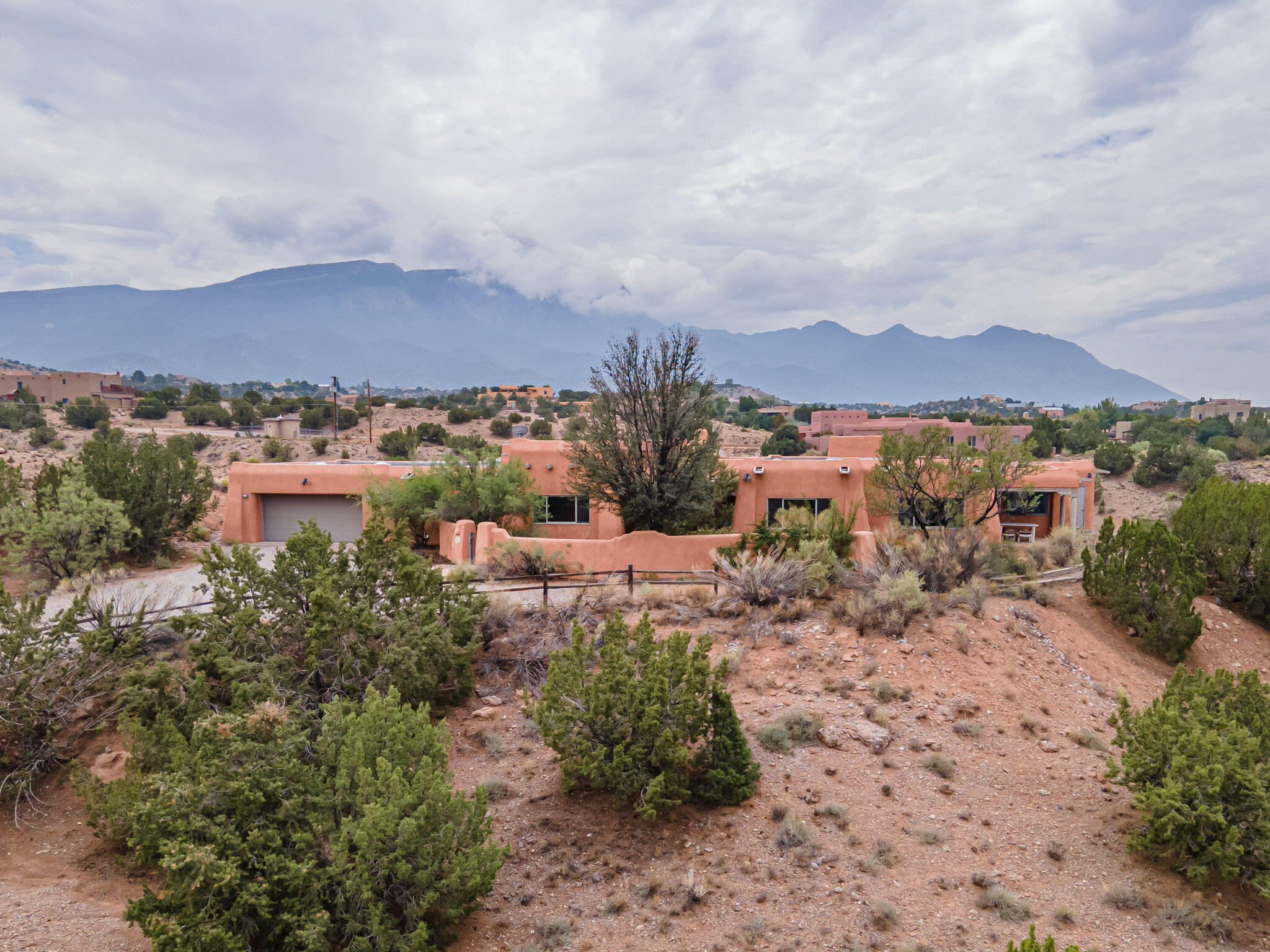 Classic charm and Santa Fe style in this fabulous custom home (feels like a resort) on over 3 acres with fabulous views! The home was designed for the lot to take advantage of all the pretty views of the Mountain and mesas.  Amazing kitchen with Sub Zero, Dacor, gas cook top and double ovens, built in desk and buffet. A kitchen island and peninsula. Nicho's, vigas, arches, adobe, willow branch inserts in the fine wood cabinets, and tile through out. 1 office, 1 studio, 1 darkroom/dog wash and two additional bedrooms. Primary bedroom has two full baths. and a swim spa. Extra storage in the garage. Formal and cozy dining space.  Several covered porches taking advantage of the wonderful New Mexico weather. Make this your next home and you will never want to leave.