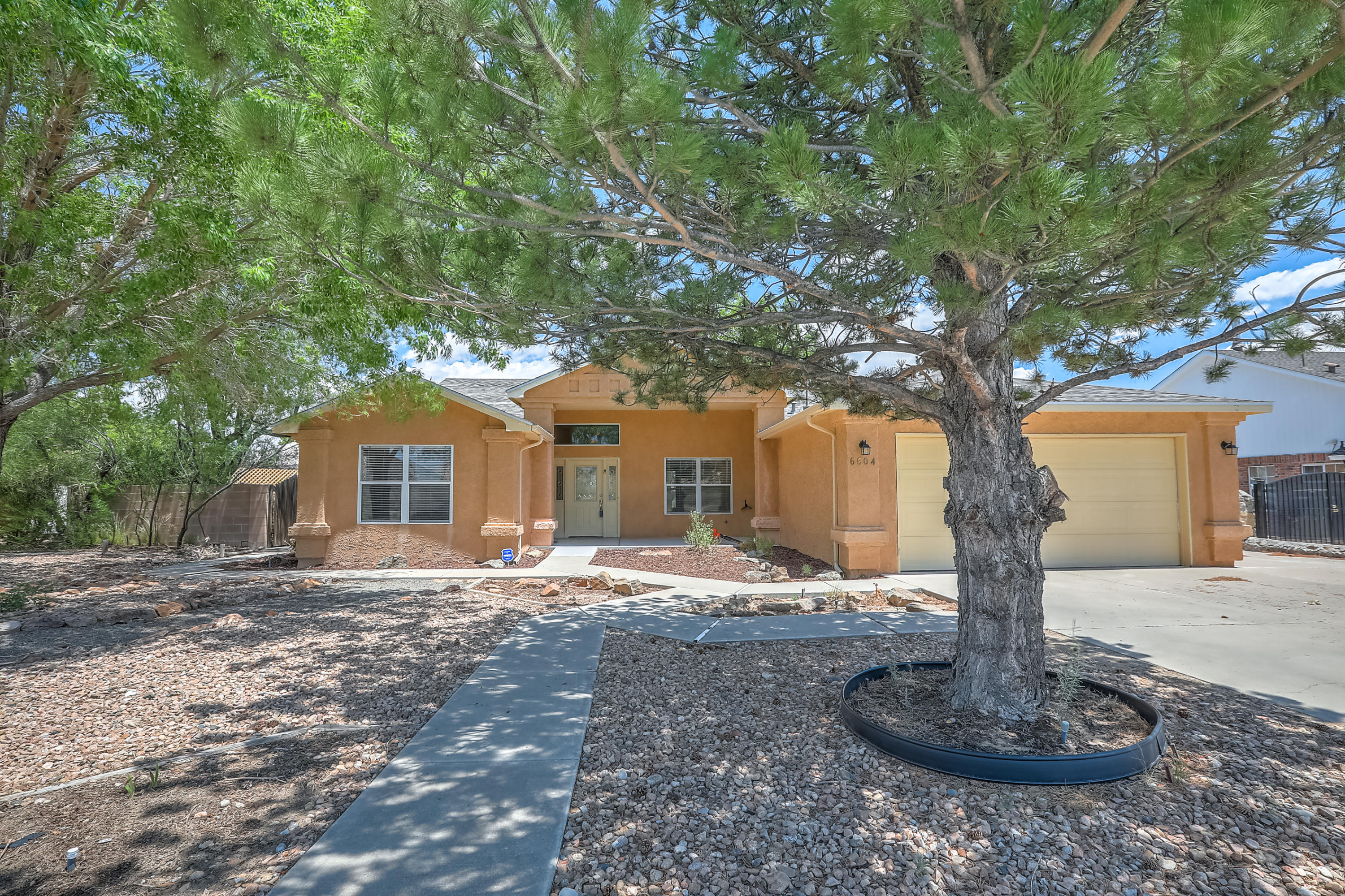 Welcome Home! This beautiful well maintained home on a large corner lot in an established neighborhood with big trees. This home is across from the Petroglyphs with hiking and trails. As you enter the home through the large front covered patio into the entry way to the left you have an over size dinning area with plenty of entraining space. Open concept with the kitchen, breakfast nook and living room. In the living room enjoy the easy low maintenance gas fire place. Master bedroom has a walk in closet and master bathroom with separate tub and shower. 3 more spacious rooms; all rooms with ceiling fans. A great sunroom for plants or extra space for relaxing. Large backyard with grass, water feature and side yard access. Come by Today.