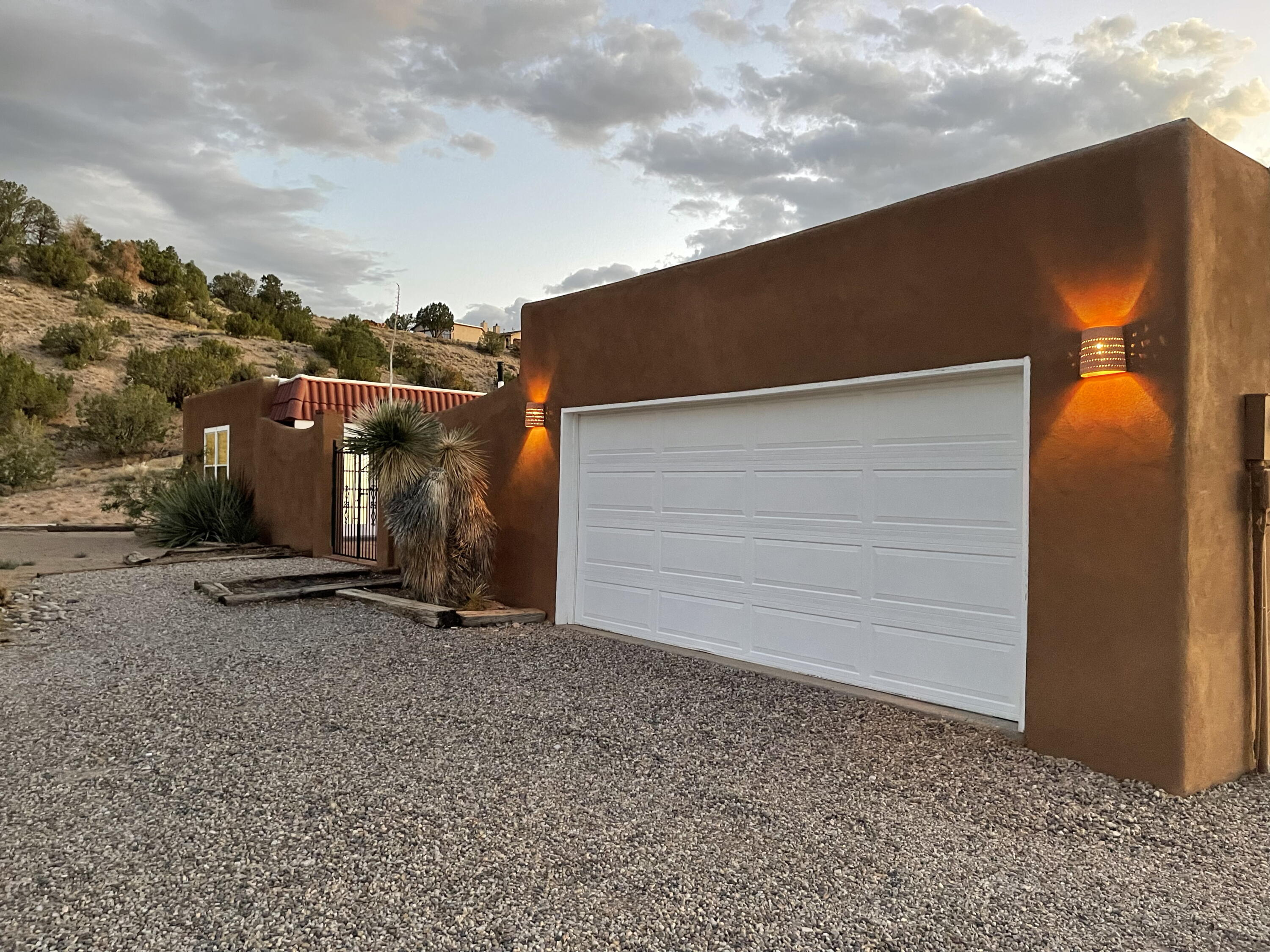 This Custom Southwest Style Home Offers Wonderful Mesa And Jemez Mtn. Views. The East Facing Front Red Bricked Courtyard Is Perfect To Enjoy The Morning Sun Or Evening Entertaining. Enjoy Beautiful Sunsets From The Extensive Side/Rear Veranda. Large Kitchen & Dining Areas. New Kitchen Appliances, Brick Floors & Cozy Wood Stove. Great Room Features Kiva F/P With Nichos. Newly Remodeled Bathrooms with New Flooring and Carpet. 3 BRs and more space. 28x24 Multi-use Building-Heated, Cooled, & Overhead Door, 220 Outlets available. Wonderful House with Open Feel, for an Amazing Price!!