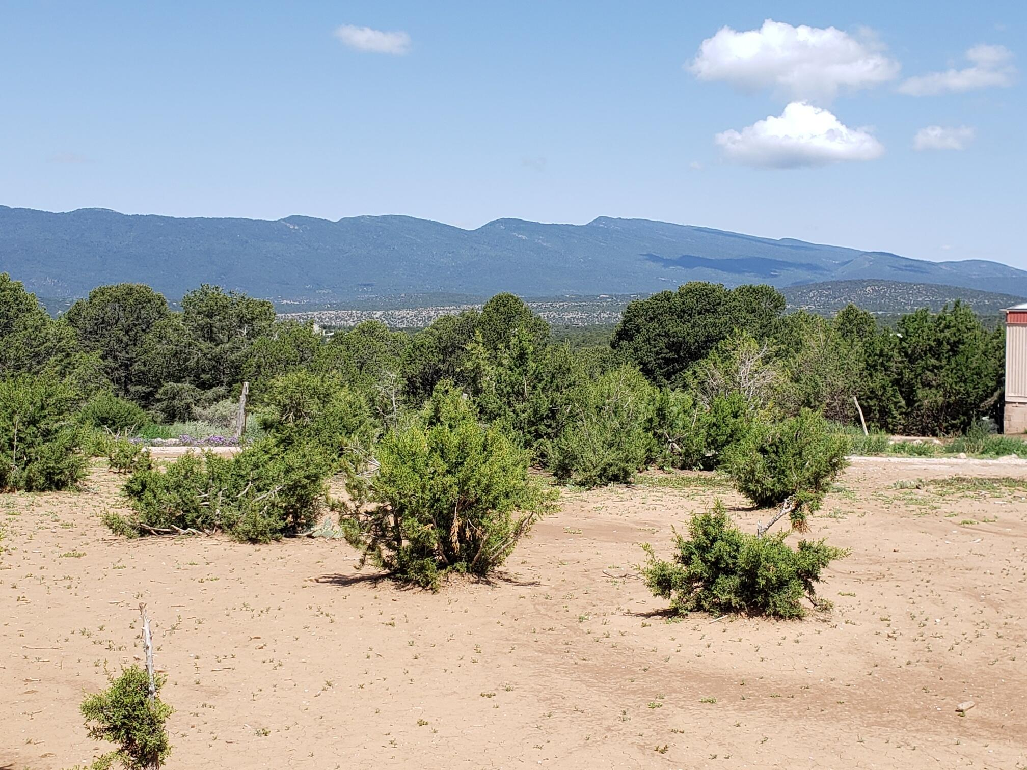 3.74 Acre lot located on a hill with views of the Sandia Mountains and all surrounding mountains. Includes 14 X 80 foot mobile home.  2 Bedrooms and 2 Full Baths. All existing furnishings stay including a pellet stove. New septic tank in June 2021. Water Tested in May 2021. Reports Available. Peaceful Quiet location perfect for a weekend getaway. Great lot to build your dream home. Short distance to Tijeras, Cedar Crest or Edgewood.