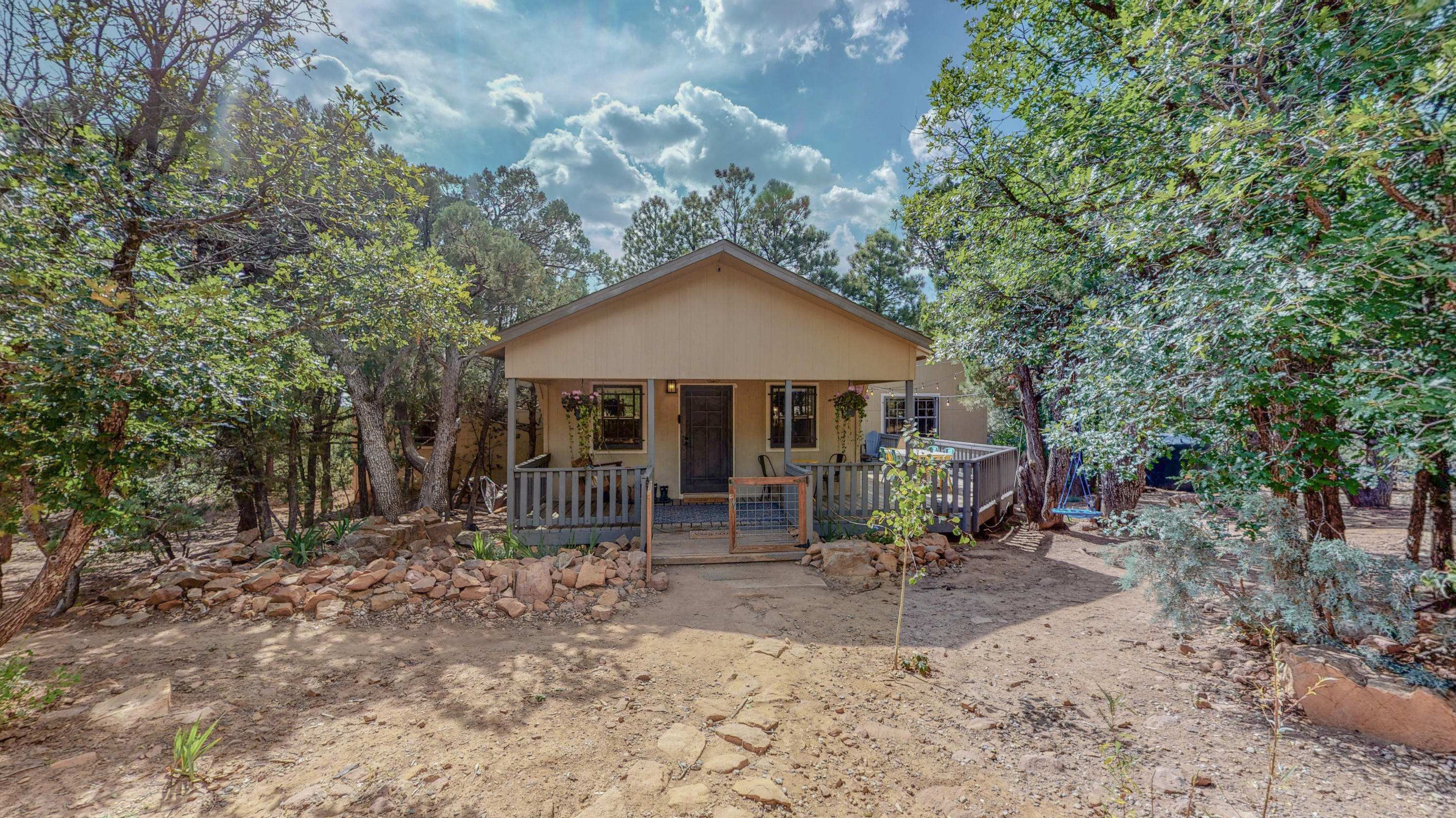 Welcome to this immaculately kept dwelling, nestled in peaceful Tijeras. The interior features soaring ceilings, vast walk-in closets, an excellent floorplan, open concept kitchen, and views of the forest from every window. Outside you'll find an entertainer's dream deck, perfect for dinners and parties, a charming porch swing to curl up on with a book and a cup of coffee, a large fire pit nestled into a clearing for gathering with friends, tons of wildlife and pockets of flower gardens scattered about the property. Minutes from hiking and camping. Gorgeous commute through picturesque canyons. Adjacent cabin property at 3 Dove  ALSO for sale by same owners. Live in the main house and rent out the cabin or use as a guest house! Great Airbnb Potential for Balloon Fiesta!