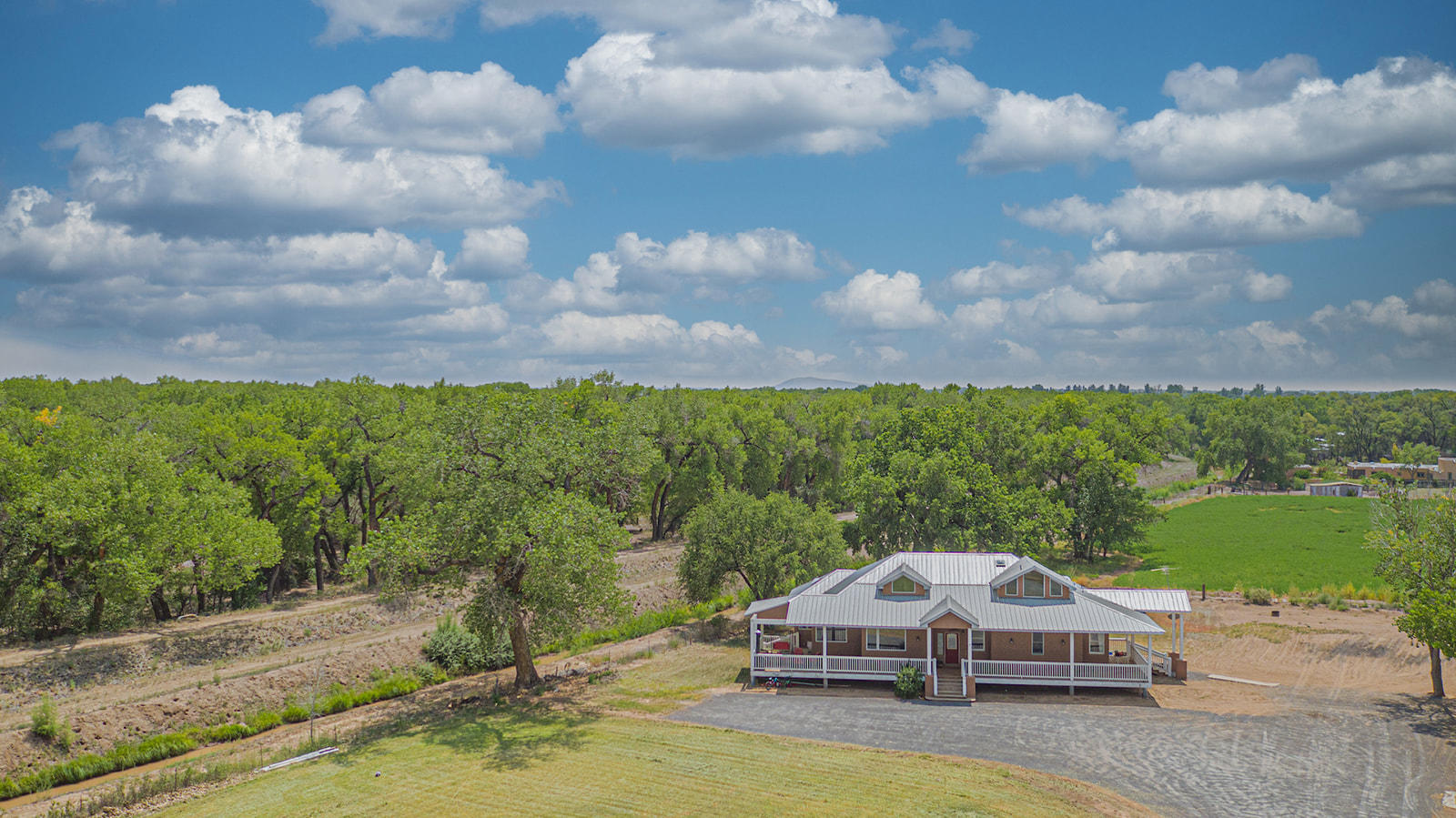 Looking for the perfect country home? Look no further! This amazing home is located against the Rio Grande River on 2 gorgeous acres in the heart of Los Lunas. This country home is complete with over 2,200 sq. ft. 3 bedroom, 2.25 bath, wood floors, large wood windows that give natural lighting throughout, refrigerated air, kitchen island, coffee bar and so much more. Come take a look at this gorgeous property with wrap around porches it won't disappoint.