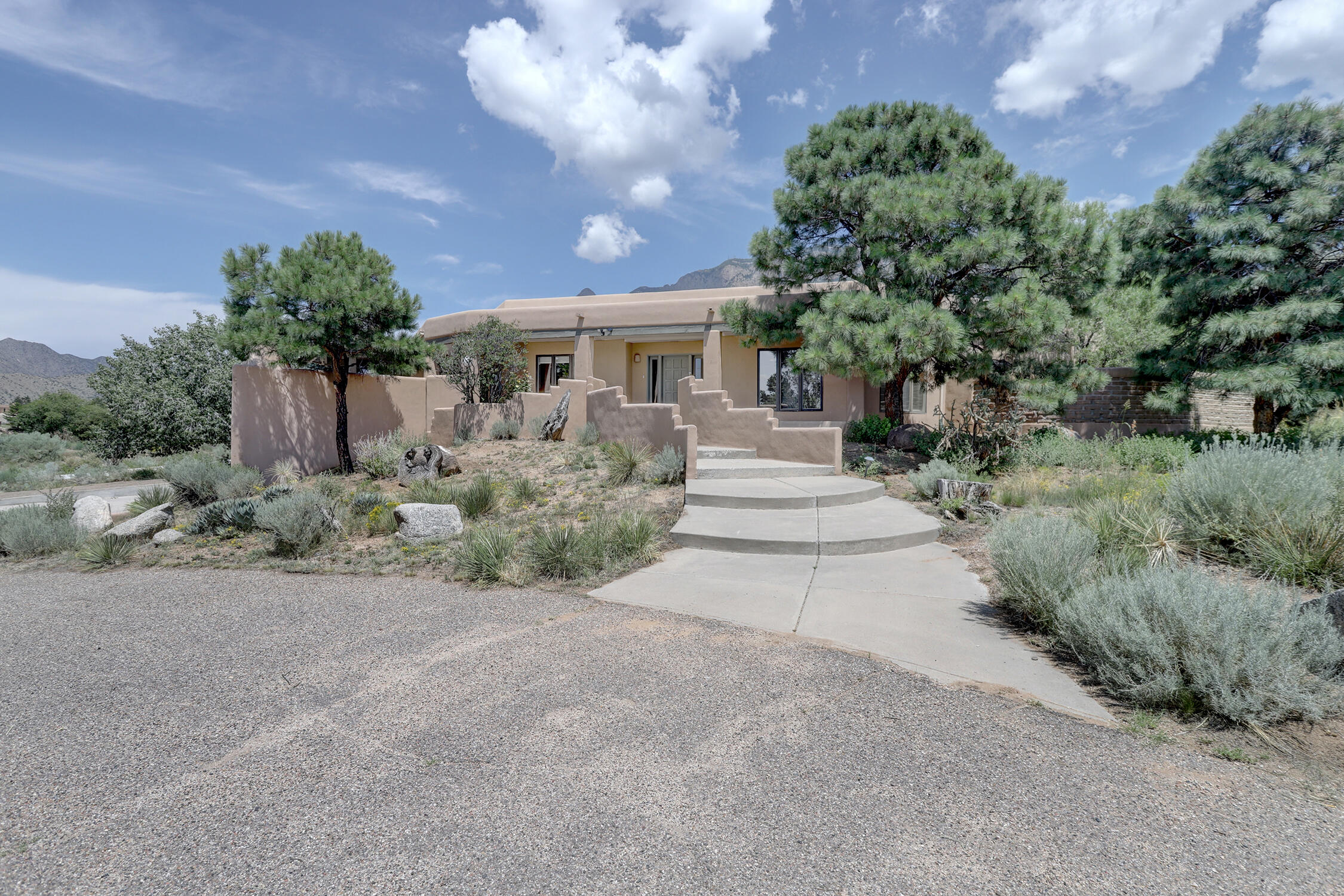 Magnificent Southwest Home. An absolute charmer nestled on a  premier one acre plus view lot! Mountain to city (east/west) stunning vistas to enjoy.  Gourmet kitchen with stainless steel appliances, walk in pantry ( with a dumbwaiter to the garage ), cozy 2 sided fireplace which warms both the kitchen and dining room areas, large pass through window to an unbelievable front deck and barbecue area, great for entertaining and taking in the city lights. Large master bedroom, private hot tub area, master bathroom (including a jetted  tub)  Great living room and den spaces for entertaining or just some quiet time. The backyard is framed by the stunning Sandia mountains. This home also provides a lower level  media / theater room, guest bedroom and 3/4 bath.