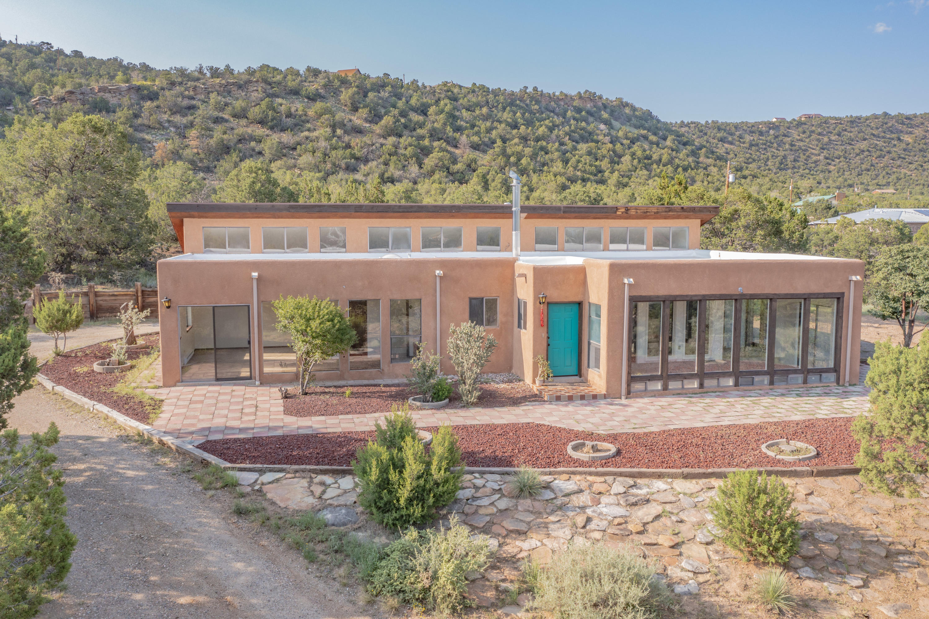 Windows, light, views! This 3-bed, 2-bath home has been built to maximize it's 3 acres with incredible views, both inside and out. Step inside the kitchen featuring solid wood cabinets, full bar/peninsula, flowing and open floor plan into the dining room/living room/family room. Natural light abounds from the copious clerestory windows and floor to ceiling picture windows from which to take in the mountain views. Another full wall of floor to ceiling picture windows rounds out the owner's suite complete with private patio access and full ensuite bathroom. Even the 800+ sq ft garage/workshop is filled with natural light from a plethora of skylights. All this tucked into a quiet mountain neighborhood and still only 15 minutes from all the Albuquerque amenities.