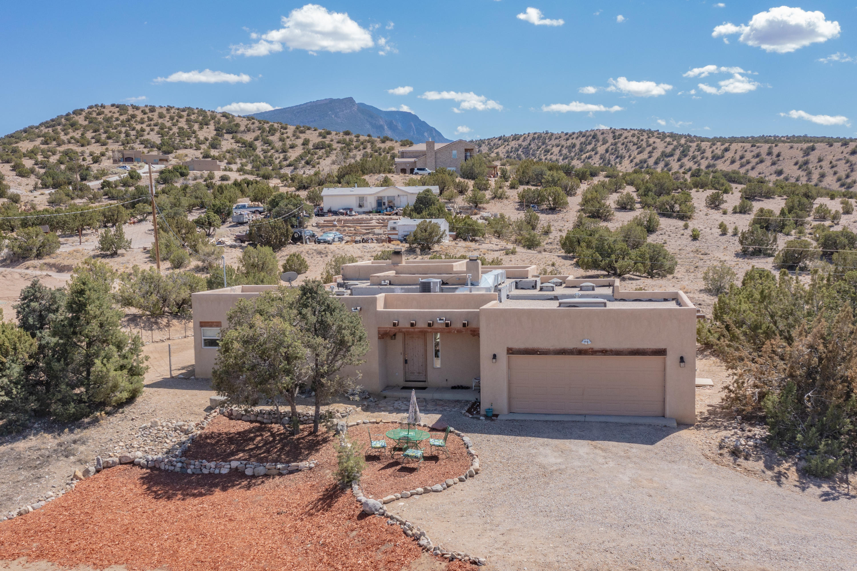 This beautiful custom Southwestern style 2 bed 1 bath home on 1.29 acres offers privacy and amazing views in the wide open Placitas high desert! 2 large bedrooms, office off 2nd living room could be a 3rd bedroom, large bathroom with garden tub & tile shower. With ample natural light from the huge windows and skylights, raised wood ceilings, 2 kiva fireplaces, adobe accent walls, and large rooms this spacious home is a true New Mexican gem! So many lovely private outside places to enjoy the breath-taking sunsets and clear night skies, plus a fenced backyard. Open-concept floorpan includes a grand foyer, large kitchen w/ granite counters, new deep basin farm sink & faucet & ample cabinet space, laundry room w/ extra storage. New house well pressure tank, leased propane tank, septic tank.