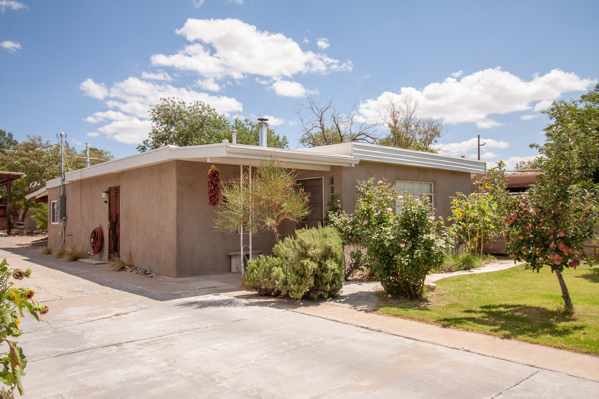 BACK ON MARKET! BUYERS FINANCING FELL THROUGH! Welcome to your urban oasis! Conveniently located near I-40, the Uptown shopping district, and tons of restaurants. This 1950's charmer boasts new floors, new roof, new stucco, automatic driveway gate, wood stove, upgraded 200 amp electrical service, and a finished (heated and cooled) artist's studio. The yard is fully fenced with the potential to grow a beautiful garden. The custom steel carport is fit for all your cars,  rv's and toys! All the custom steel security doors and extras really make this home special. Pride of ownership is an understatement in this home that truly make it a gem. Don't miss this chance to own a great home!