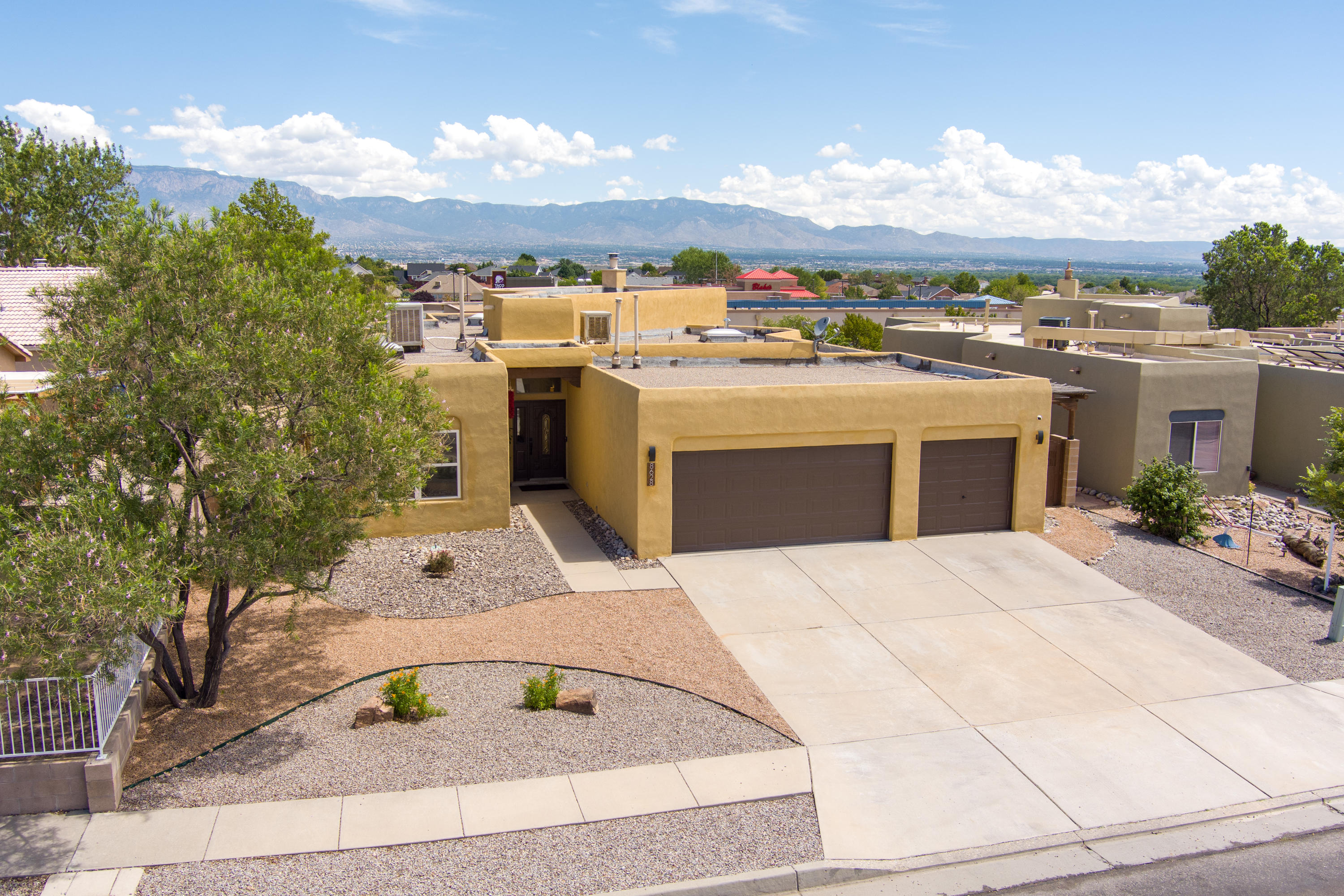 Welcome to this stunning 3 bedroom, two bathroom, three car garage home with unobstructed mountain views! Conveniently located near Paseo Del Norte on a cul de-sac in the highly sought after Piedras Marcadas, with private access to Petroglyph trails and a wonderful park. Features vaulted ceilings, skylights, hand made vigas and a wood burning kiva fireplace. Oak floors, modern lighting, updated cabinets and granite countertops complete the modern southwest design. The master suite features a gas fireplace and gorgeous custom walk-in closet by California Closets. The updated kitchen features a gas range, stainless appliances and tons of storage. This combination of fantastic location and tasteful design won't last long!