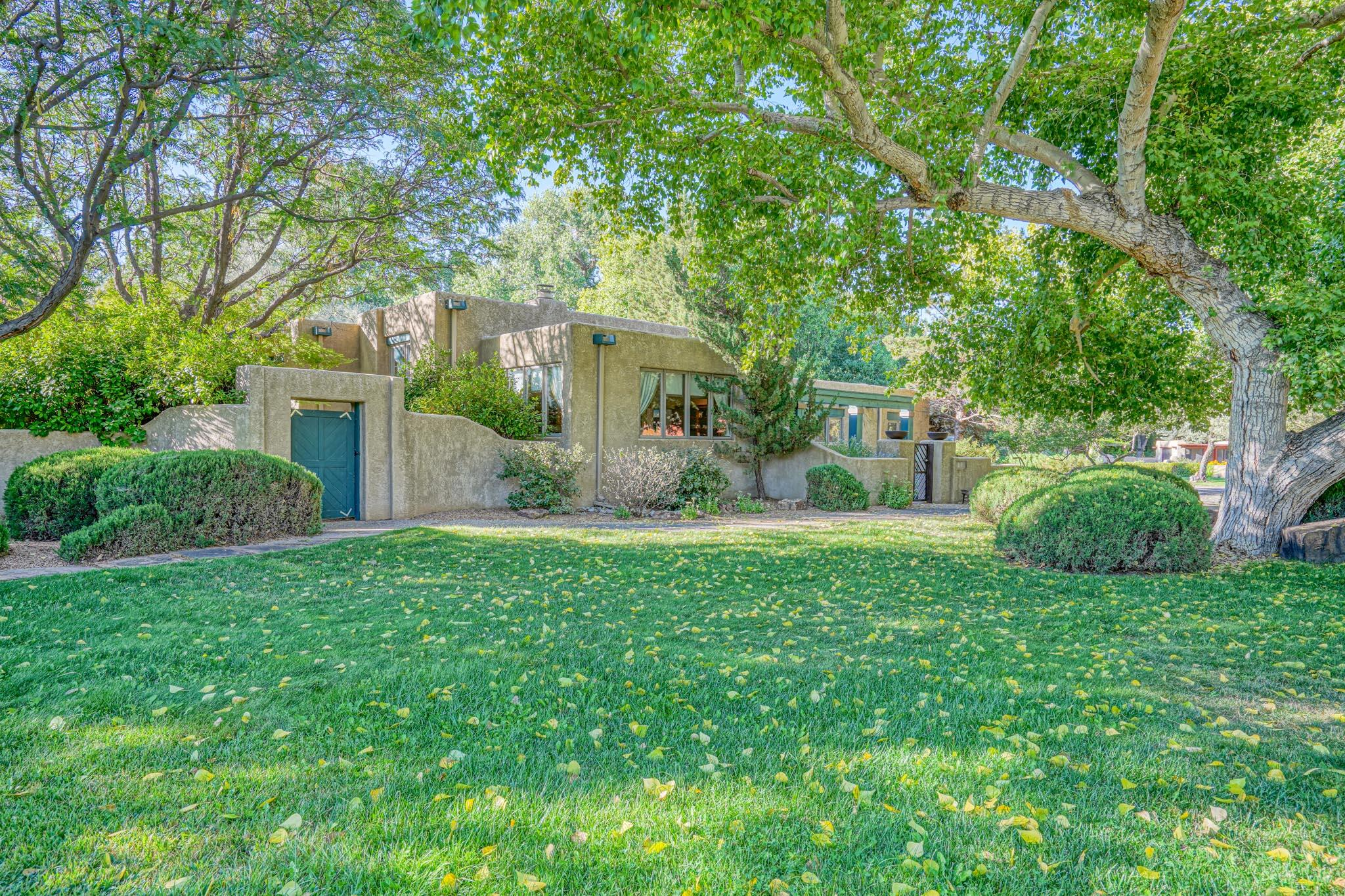 Beautifully refreshed one level oasis on idyllic acre in coveted Tinnin Farms Neighborhood of Los Ranchos de Albuquerque. Perfect cul de sac location, steps away to miles of Bosque trails, Rio Grande River and Los Ranchos Farmers Market. Stunning updated owner's retreat. High ceilings, open spaces & warm cozy spaces. 3 bedrms, full office and flex room. New since 2016: hardwood & brick floors, entire interior painted, new SBS roof & skylights, 2 new aero-coolers, new boiler for warm floors in winter. Nestled amidst private lush mature irrigation 'well' watered trees and lawns. Great Indoor outdoor flow beckons you to private courtyards and a 'botanical garden' experience of paths, hummingbirds, wildlife, pergola, rose garden, fruit trees and rock waterfall.  Many more details attached.