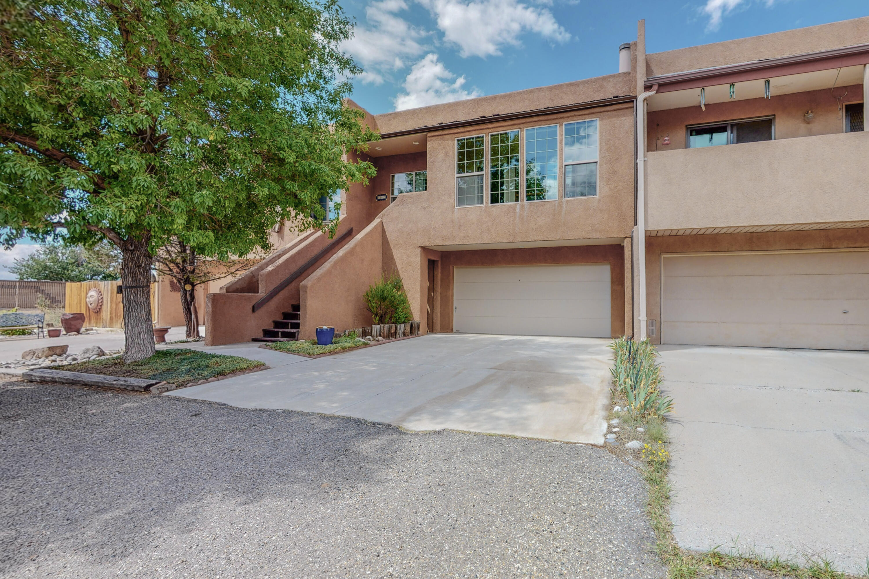 This large two story townhouse (2100+ square feet) in Sandia Heights in the Sandia Mountain foothills offers a large open living, dining area with mountain and city view. There are two possible master bedrooms and many upgrades include a TPO roof and skylights, 2020, water heater and heating boiler in 2021, new stucco 2019.  Remodeled baths and tile floor in kitchen and new cooler and windows in 2014. There is a country feel open space in front and close access to bike/jogging paths and hiking trails. The back courtyard is minimal maintenance The interior is bright and airy with 9 skylights.  There is ample storage and an oversized garage. The entry foyer/sunroom is a nice area to relax in and it provides passive solar heating for the home. Check out this Sandia Heights townhouse NOW!