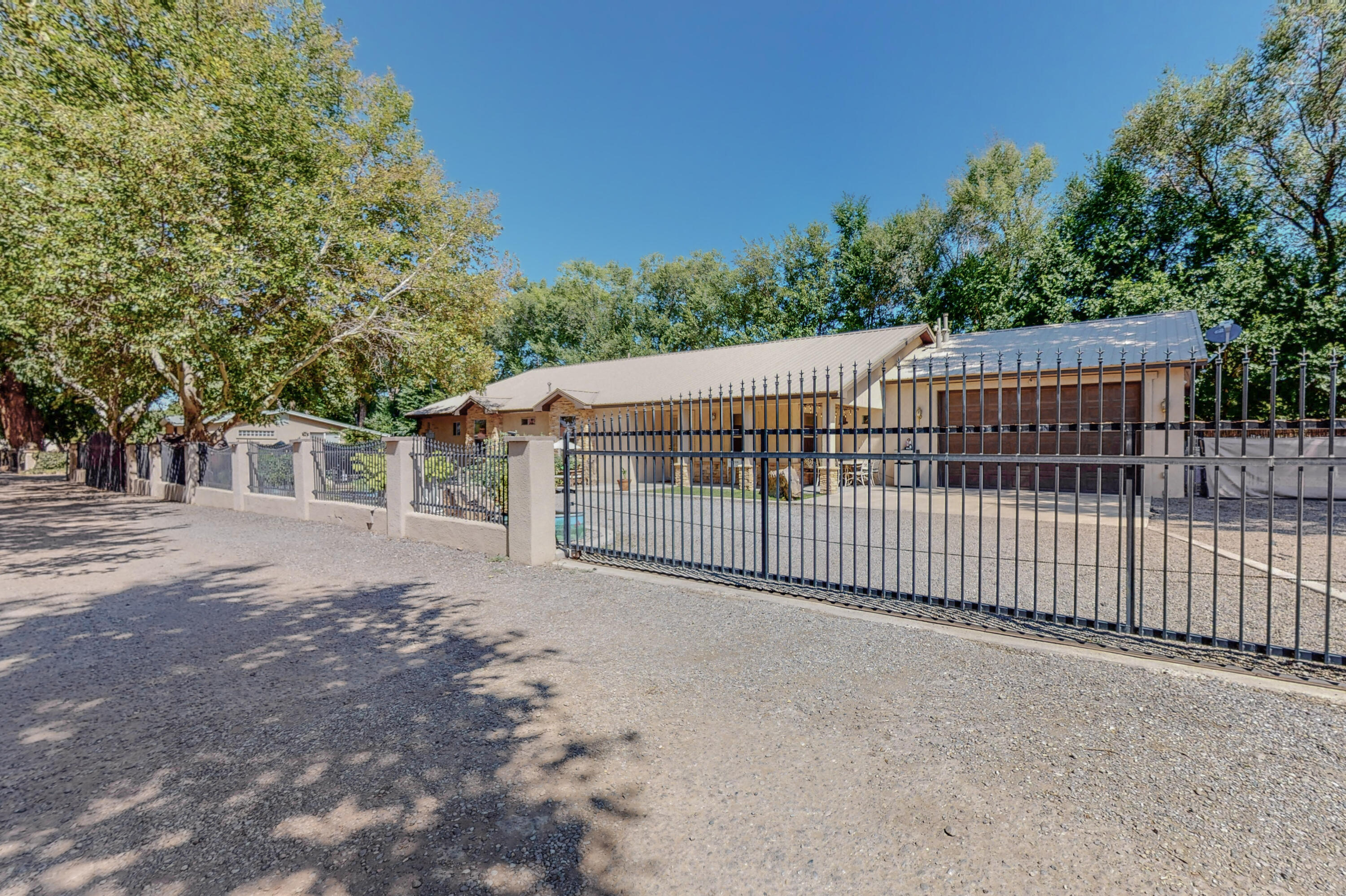 This private North Valley home is situated on a very private 0.38 acre lot. There are only 4 lots in the cul-de-sac with a private main gated entry and the home is also fully fenced with its own private entry gate, latia fencing was recently added to the back fence. The location offers very quick access to I-25 and only a few hundred yards from a Rail Runner stop, this home is ideal for commuters. This unique floor plan is truly one of a kind. The home is very open and spacious, great natural light, recent updates include wood panel accent walls, recent paint. Kitchen is open with a breakfast bar and separate dining area. Large front porch and back patio for entertaining on warm summer nights. This home is truly beautiful. You have to see this property in person! Schedule a showing today.