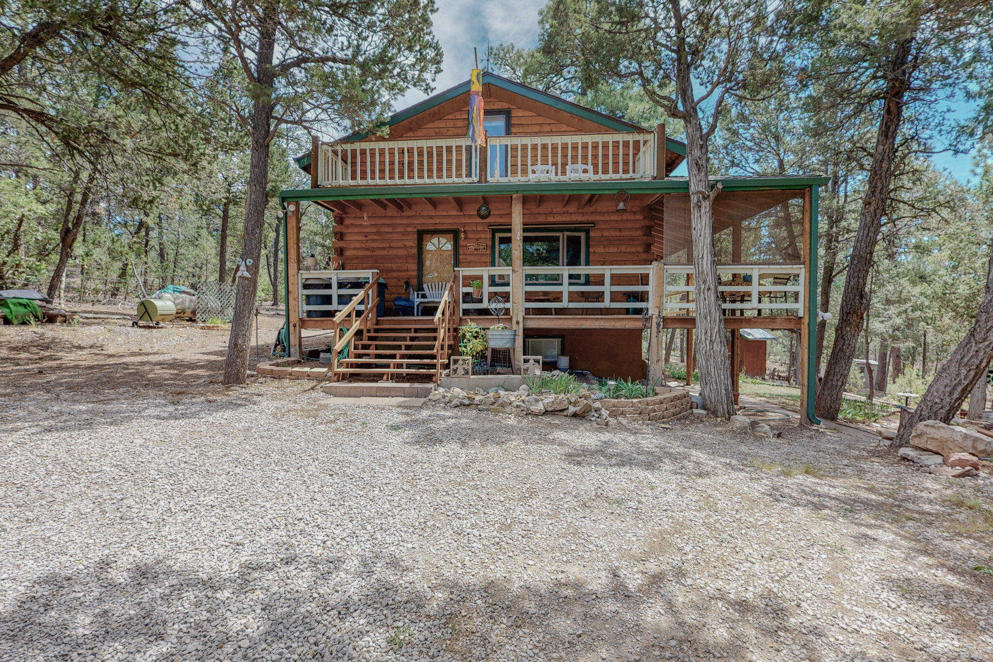 Enjoy peaceful comfort in this cozy cabin in the woods. Three levels offer lots of living options. The main floor has two sides wrapped in decks, there's a balcony on the upper floor, and the walk-out basement has a sheltered patio. The putting green lets you keep up your golf skills and the huge 30x30 detached garage has room for cars, trucks, and toys. Plus a 2-car carport and RV shelter. Garage has an 30 amp RV plug.  Radiant and baseboard heat, gas and wood fireplaces, and double and triple paned windows, keep all the levels warm and toasty. The 848 s/f walk-out basement is fully finished with fireplace, kitchenette, bedroom, walk-in closet and 3/4 bath, with a  separate entrance. (Basement not included in home square footage.) Property is fully fenced with a gated front entry. Enjoy!