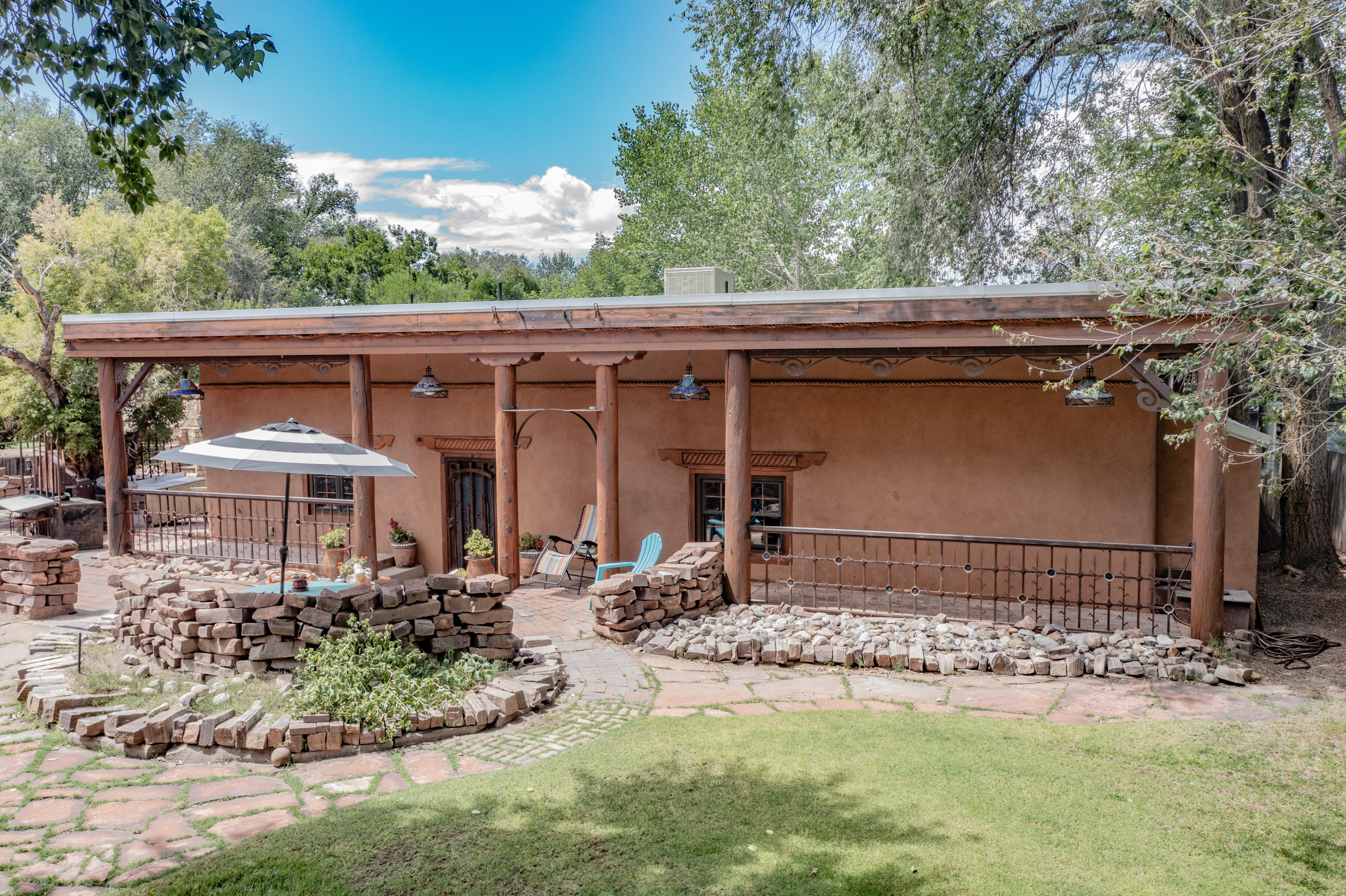 This unique north valley property offers it's own private paradise on 1.35 acres.  The main house has 3 bedrooms, 2 baths, radiant heating, beautiful polished concrete floors and venetian walls, all adobe.  The guest house, built around 1936 is also made from adobe, has 3 bedrooms, 1 bath, original wood floors, quaint little kitchen with Spanish tiles.  The 3rd building is only 6 years old and has a beauty salon.  All 3 buildings over look a beautiful pond, waterfall and grass area, all provided with water from an irrigation well.  All properties are on public water and sewer.  Many fruit trees, large metal gate for privacy and plenty of parking.  Workout room with sauna.  Several storage buildings. See Melanie for exclusions.