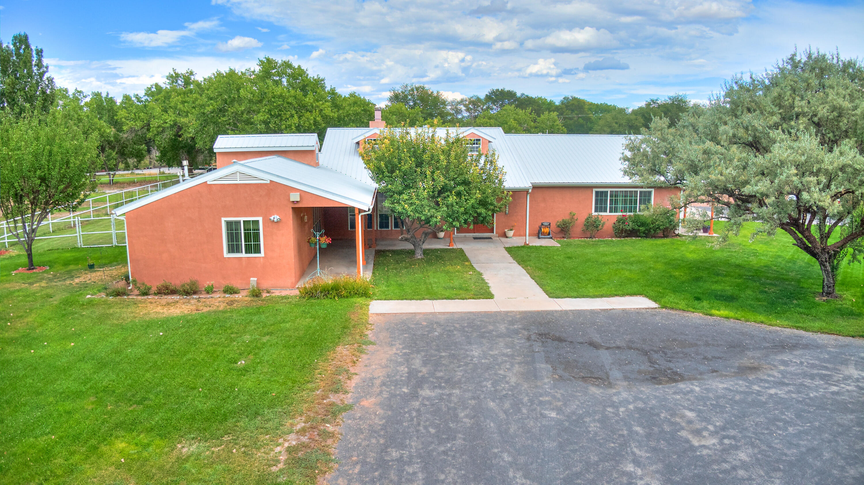 Welcome! Lovely Northern New Mexico style home situated on 1.46 acres on treelined cul-de-sac in the verdant South Valley. Tired of the hustle & bustle of the City? Come on down! This custom home designed by John Freidman offers 4 BR's, 3 Baths, oversized 3 car garage plus 16 x 16 heated & cooled professional glass enclosed recreation room with pool table or perfect for home office or home schooling. Amenities include wood ceilings, hardwd & tiled flrs, nichos, clerestory & dormer windows, vaulted ceilings, wood burning fireplace,  country  Kit, separate owners suite & more. Updates: furnace & 2 AC units 2012, roof tune-up 2021,sprinkler system 2021 & almost all windows including the dormer windows have been replaced. Fully fenced backyard plus separate fenced corral. City Sewer. Well.