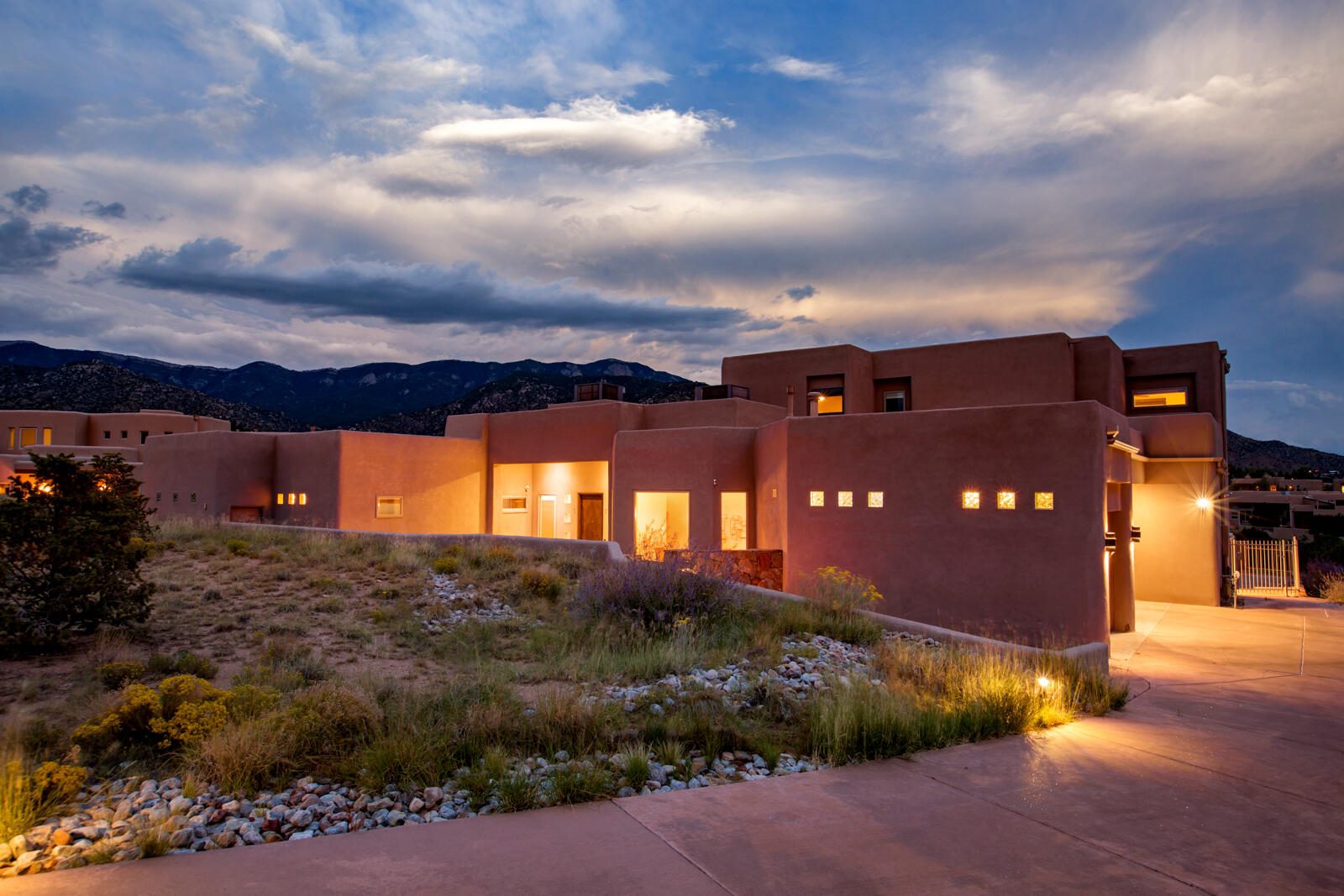 Take a look at this incredible find in High Desert. This custom home was designed to take advantage of the amazing views of the Sandia Mountains, and the city lights. This home features a bright and open floor plan with quality finishes including beautiful wood windows, Alder custom cabinetry, rich granite, wood interior doors, stacked stone, and porcelain flooring. The primary suite and one guest bedroom are on the main level, and upstairs there are 2 more bedrooms, a loft and an office. Enjoy outdoor living from the large patio with a water feature. Security system with cameras, an audio system, and owned solar convey! Enjoy the best of the High Desert Lifestyle with great hiking, walking and biking trails immediately within the community, and shopping, dining & entertainment nearby.
