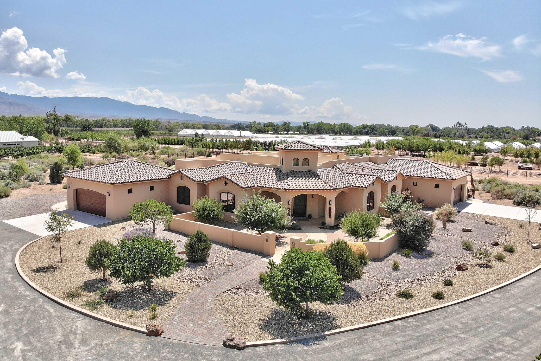 Spectacular custom home on 2+ private acres steps from the Corrales bosque w/ its miles of walking trails & cottonwood forest. Flooded w/ natural light, this luxurious property features a chef's kitchen w/ a huge granite island, walk-in pantry & state-of-the-art SS appliances that opens to a magnificent living room w/ a handcrafted stone fireplace, custom fixtures & stunning mountain views. Tavertine floors grace the interior, w/ the spa-like master in its own wing boasting his/her closets, limestone tile, snail shower & exercise room. Interior & exterior spaces are seamlessly integrated, w/ mature lush garden bursting w/ color & texture. An outdoor kitchen, 3 separate yards & a kiva fireplace make this ideal for entertaining. Close to all amenities. Corrales living at its most elegant!