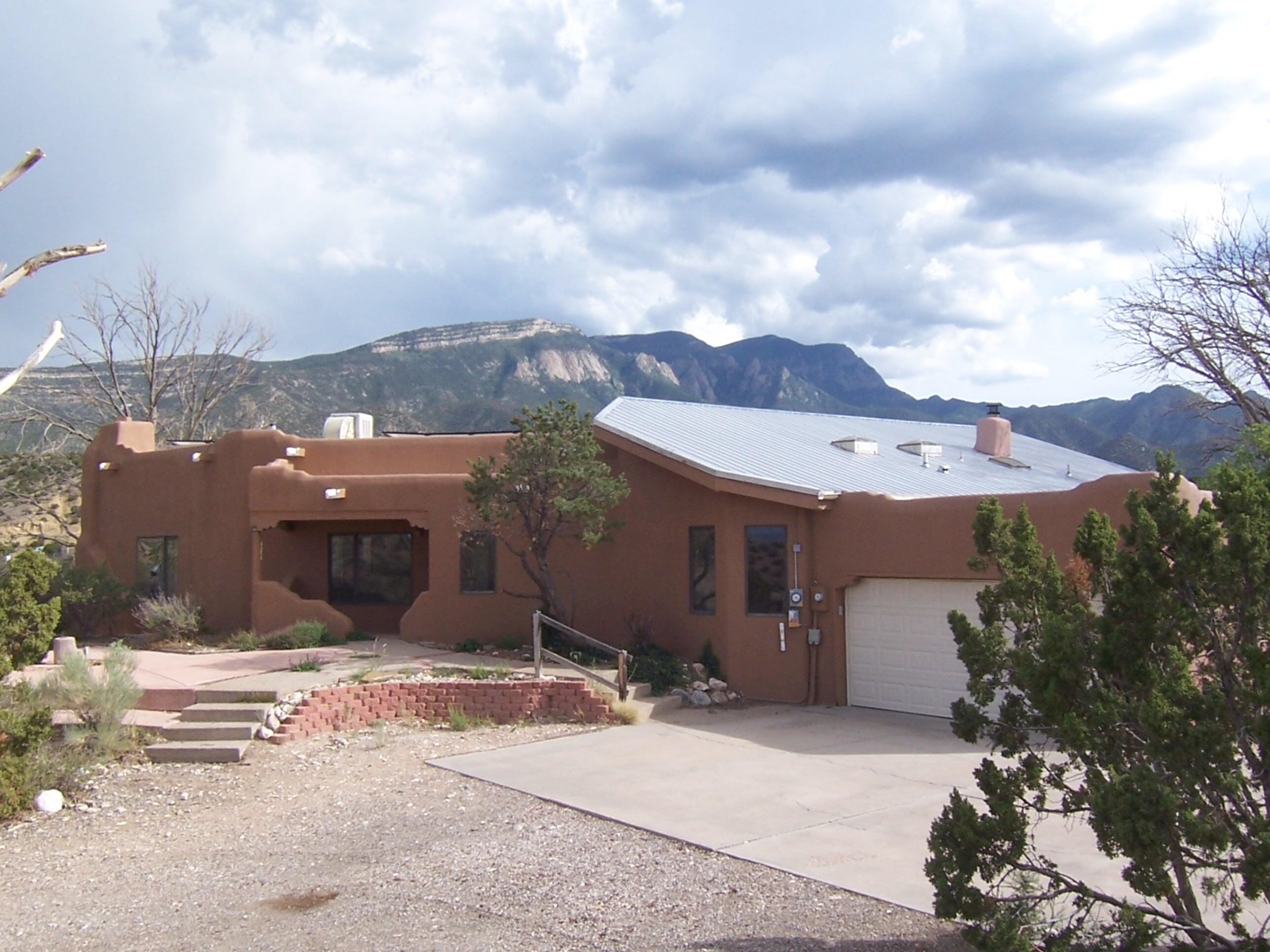 SOUTHWESTERN STYLE ON 2 ACRES! $440,000. Ridge top custom 3 bedroom home with dramatic views of the mesas and Sandias! Lots of exposed adobe and beam and wood ceilings, 2 kiva fireplaces, brick floors, open floor plan, heated sunroom, skylights and wood windows. New roof is just 2 years new! 2 car finished garage. 2 acre lot which includes over 150 feet of ridge land to the south of the house... Solar panels (owned). Views from every window. Private covered porch off master bedroom and spacious rear patio! Kiva fireplaces in great room and master bedroom. 2 full baths, walk-in closets, clerestory windows and wonderful, open kitchen with island. Community water! New septic system! Great sunroom for passive solar heat and growing plants in winter. Less than 5 miles from I-25.