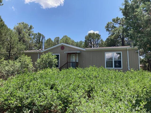 Privacy in the woods! This Tijeras home is in a quiet, peaceful area on 2 acres that backs up to hundreds of acres of NM trust land. Great access for hiking or walking your dogs. This 1680 sq. ft. 3 bedroom, 2 bath home hasan excellent floor plan with a living room, family room, and the master bedroom separate from the other two bedrooms. All appliances included: refrigerator, stove, anddishwasher. This property has a producing well and a 2000 gallon holding tank. Also included are two sheds: a larger shed with electricity, and a smaller shed for tools.This home is a 25 minute drive to Tramway/Central.