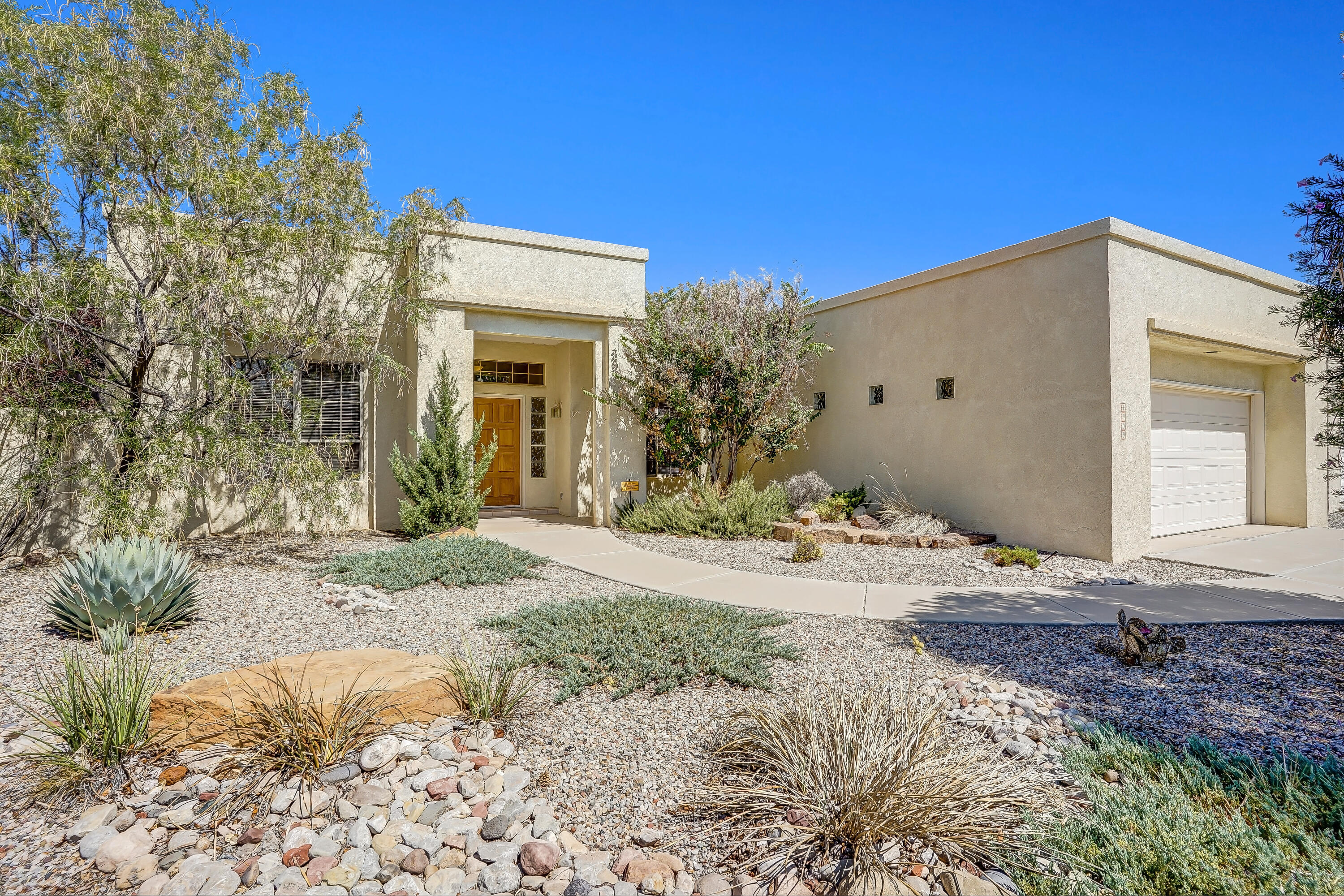 This move-in ready, three bedroom / two bath home, sitting on a nice corner lot offers comfortable living space in a convenient location. Formerly the model home for Ashot builders; the home has two living areas, a beautiful kiva style fireplace, and a wonderful backyard - perfect for entertaining and relaxing under the covered patio or enjoying a swim in the in-ground pool. The modern twist on southwestern style combines wonderfully with the ample windows to create a naturally bright, open feeling. Located in the master bathroom are double sinks, elegant large garden tub, separate showers and a roomy walk-in closet. The kitchen boasts plenty of countertop and cabinet space - perfect for the home chef's creations, whether they be formal dinners or refreshments for a pool party.