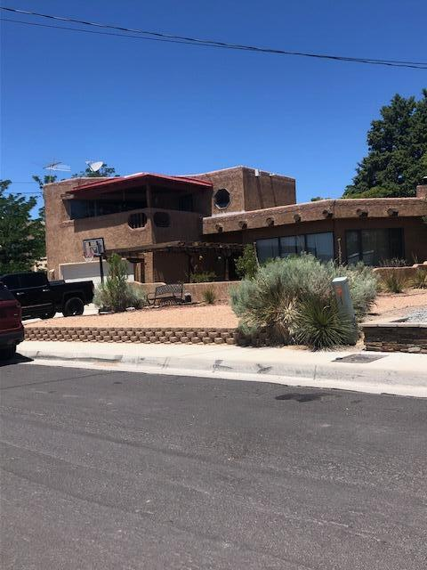 Multi-level Pueblo Style 3 bedroom home in the NW Heights.  It has brick floors in the main areas and carpet in the bedrooms.  Vigas and Latia's in the living area, Wood burning fireplace, bancos,  Kitchen has granite tile countertops.  Great backyard with grass and lots of trees.  Covered Patio.  Views of the Sandia Mts from the upstairs balcony.  Large Master Bedroom with sitting area.