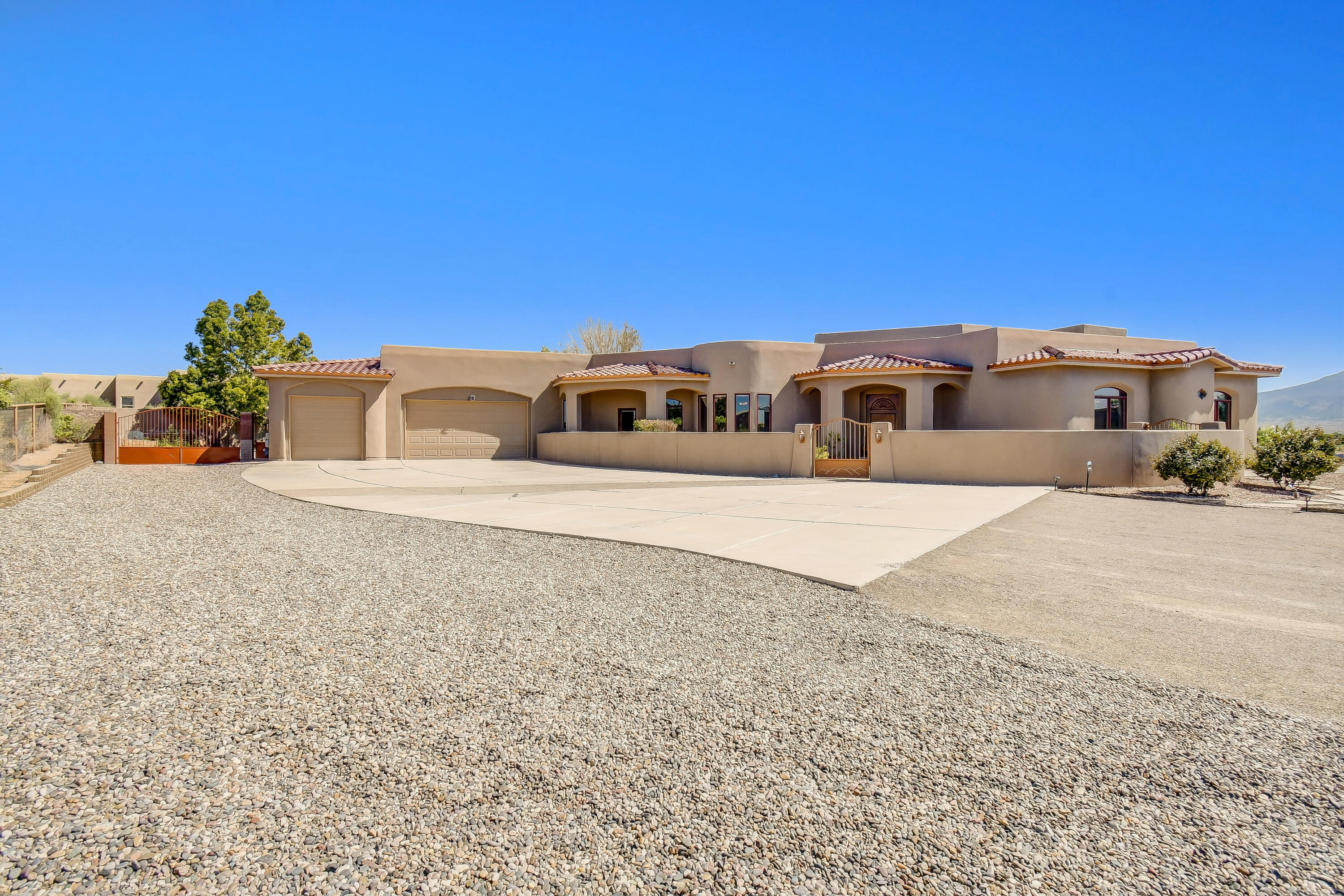 Corrales at it's finest.  This custom built home is situated on a large lot with breathtaking Sandia mountain views.  Floorplan features 4 bedrooms and an office with it's own entrance.  Natural light pours into the kitchen which features custom cherry cabinets, a large island, bar top and prep sink.  Detailed woodwork and large fireplace invite you in to enjoy cozy evenings.  Oversized outdoor kitchen area is a dream for entertaining.  Perfectly landscaped with  grass, a newly added pool and side yard access! Conveniently located off of 528, do not miss your chance, come see us today.
