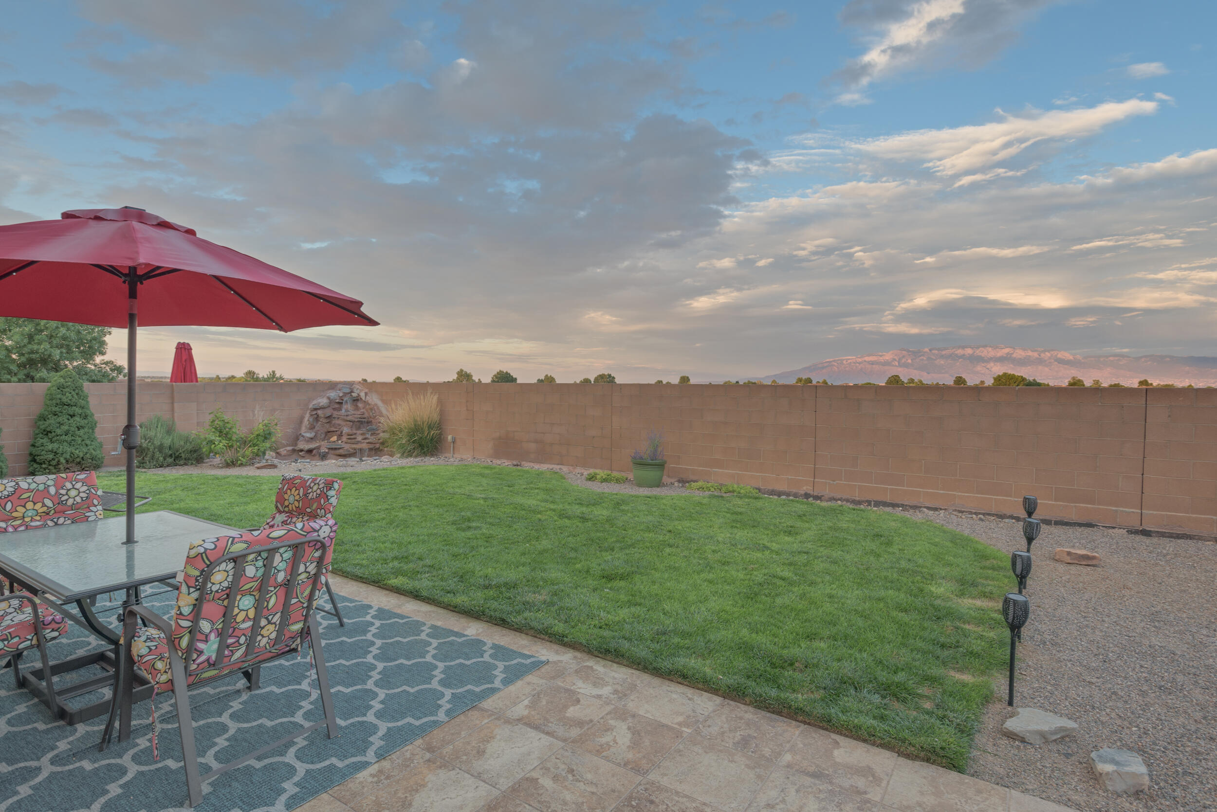 Welcome Home! This two story home offers the master bedroom on the main floor for all ages with a full bathroom & walk in closet with plenty of space.  Enjoy the beautiful open floor plan with kitchen and living room connected for entertaining.  The backyard is one of a kind in this area with no obstructed views of the Sandia Mountains and nightly NM sunsets to sit back and enjoy. Relax with the custom water feature in the corner that washes your worries away for the night. There is also separate dog run area. Upstairs you will find two additional bedrooms with a full bathroom along with a very large loft area that could be multiple things, you can even see the Sandias from there!