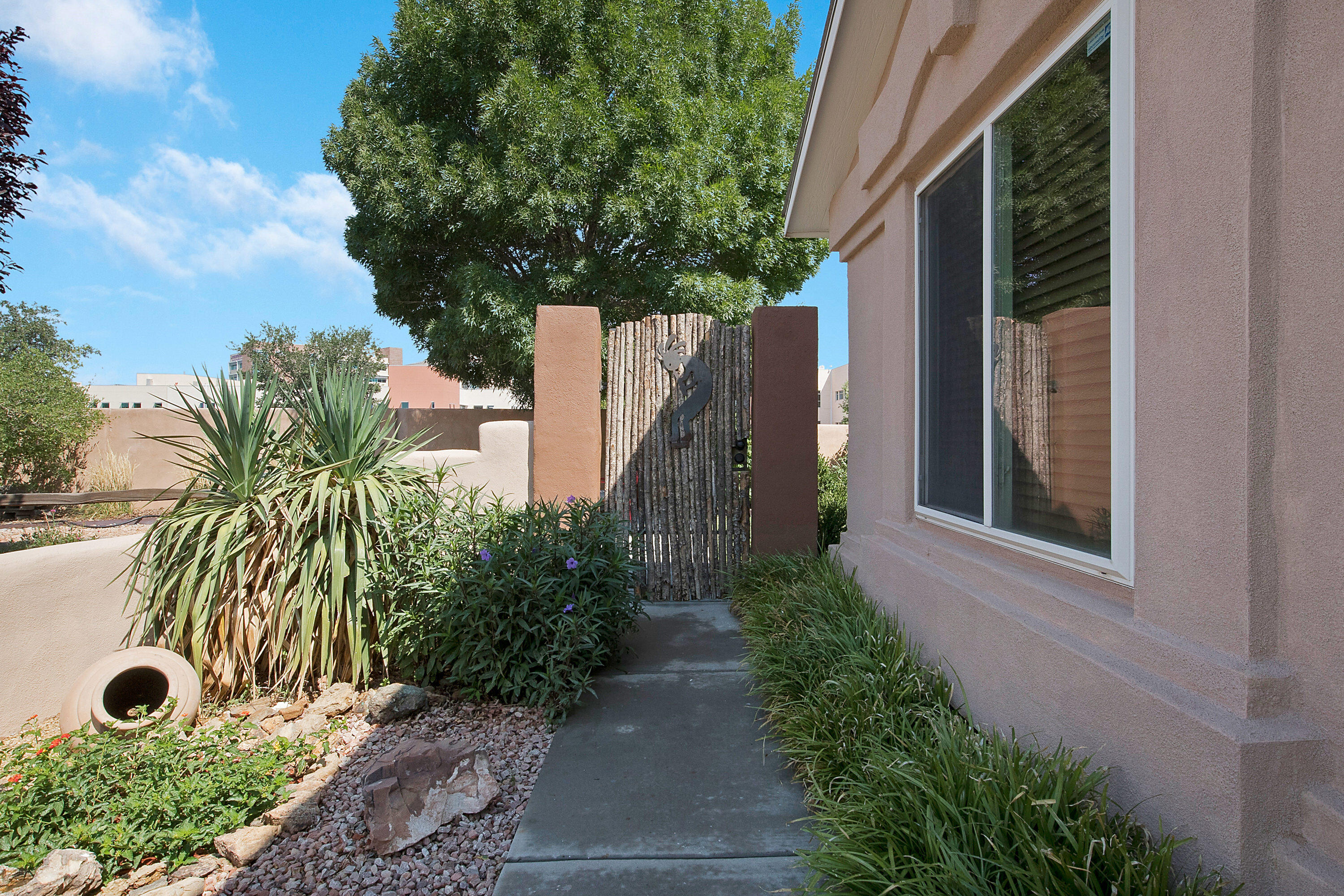 Gorgeous, green, gated courtyard welcomes you to this beautifully updated 3 bedroom home with custom touches throughout. Custom tiled foyer opens to the large living room with elegant stone fireplace and built in entertainment center. Adobe pony wall separation into the family dining room and kitchen. Kitchen features include new kitchen backsplash, granite counter tops and full appliance package. Large, split primary suite with full bath and walk in closet. 30 ft RV pad site with 30 amp hookup and 15 ft. wide secured entry gate. Shade & pine trees to enhance the rural tranquil custom Southwest Patio with built in planter, flagstone patio flooring and gazebo in the backyard. Fully fenced for privacy. Located with all the necessity: schools, hospitals, stores, storage facility.
