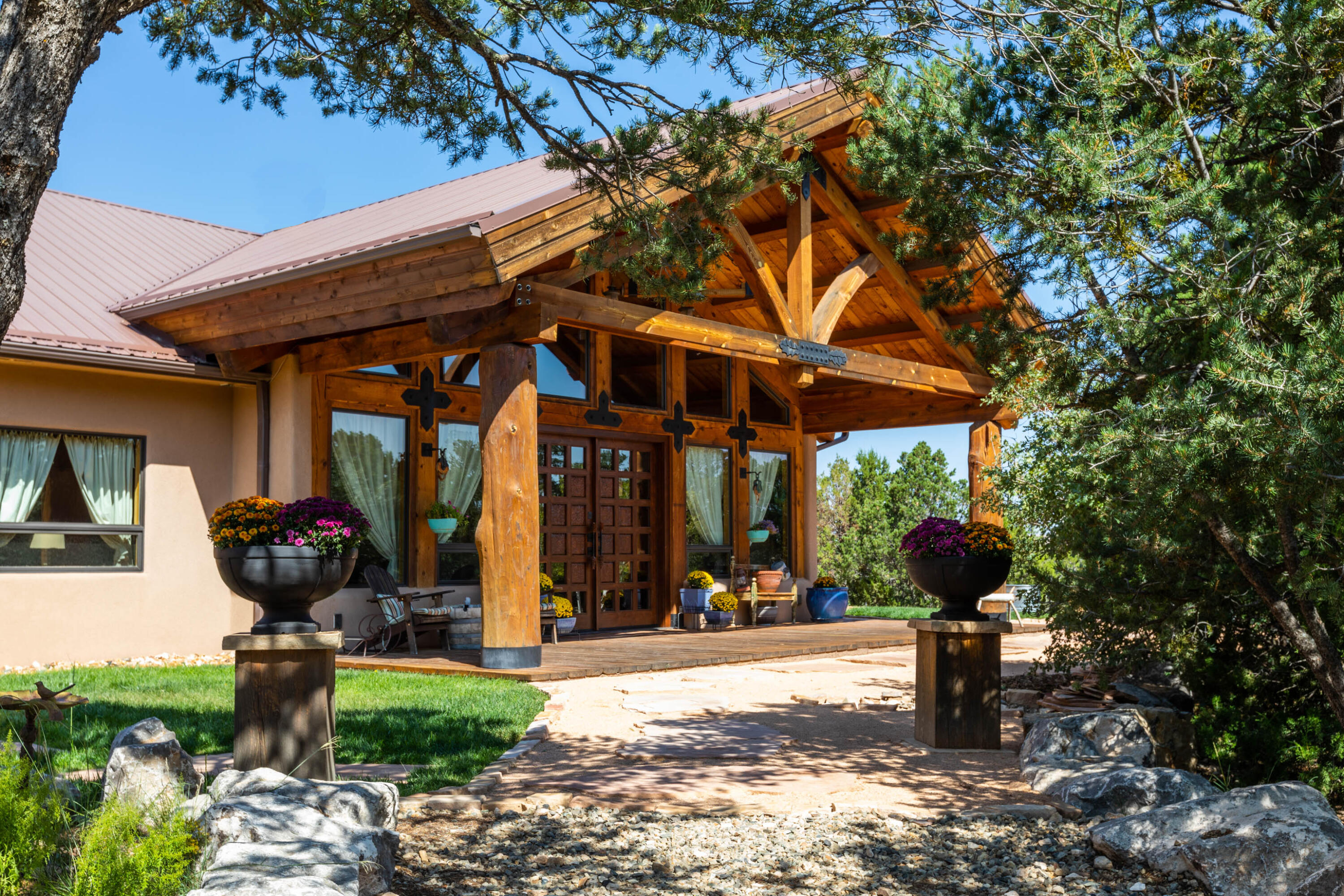 NM meets Vail, Co in this casually elegant contemporary rustic lodge. Enjoy all 4 seasons from walls of windows. 20 ft wood ceilings & massive trusses in the great rm w/2 living areas divided by a 2 way stacked stone fireplace & beautiful water feature entry. Concrete radiant heated floors & wood ceilings thruout. Kitchen has 2 ranges, 2 dishwashers, built in fridge, rainforest marble island, copper hood/backsplash & lg. pantry. Custom 12 ft+ dining table stays w/ built in china hutch. Main suite w/Jacuzzi tub, bed & breakfast fireplace & boutique closet. 1369 sq. ft. 3+ gar/workshop w/shelves. Roomy fr/bk porches, Gated/paved clubhouse community offers walking trails, indoor pool, gym, tennis, etc. The Lodge at Nature Pointe offers a remarkable lifestyle. Minutes from ABQ/Yet a world away