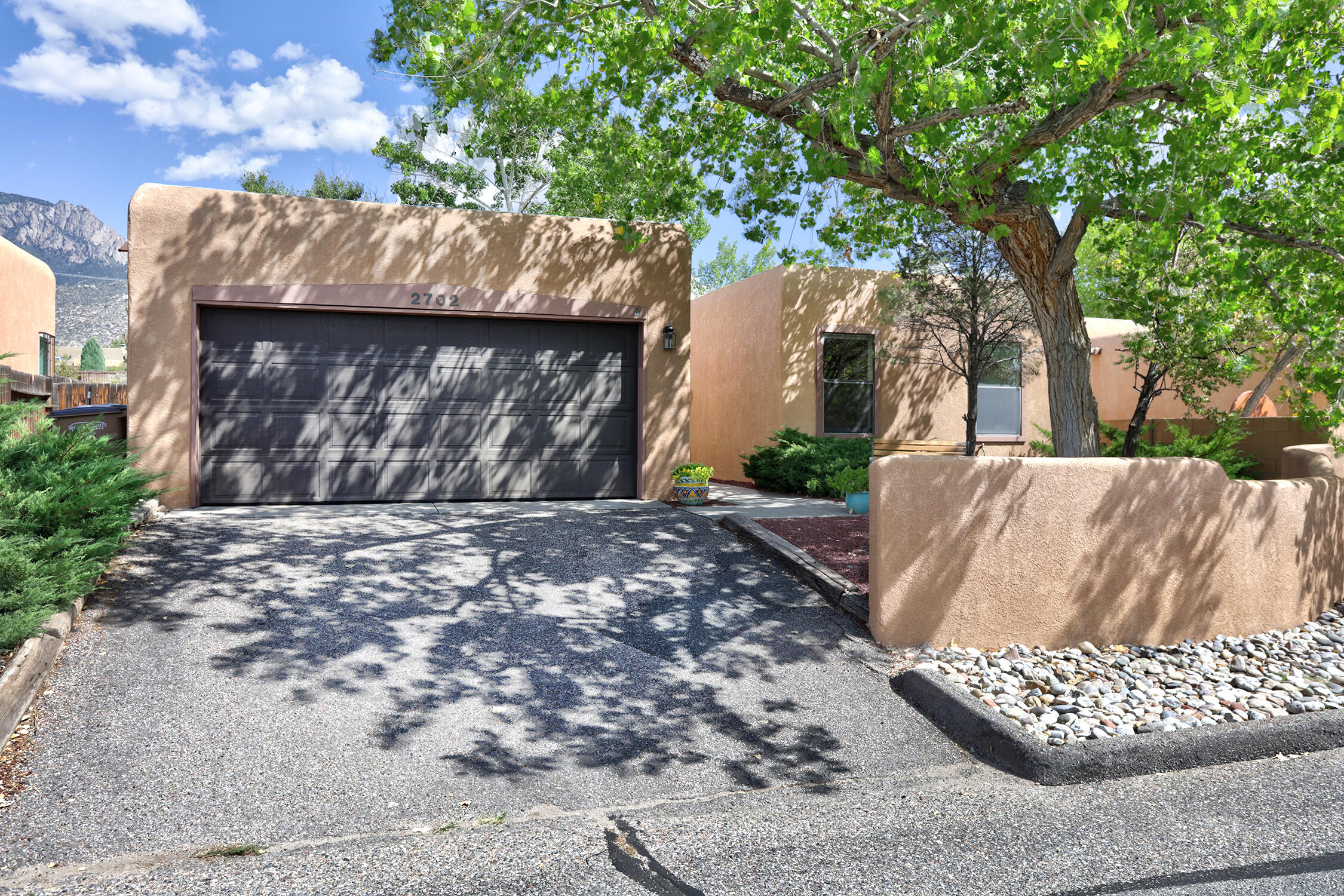 How about a beautiful home to host the Holidays! Don't miss this well-maintained pueblo-style gem conveniently located on a quiet street in Sandia Heights! Approach the sweet front courtyard & fall in love with the detail & thoughtful planting of natives & perennials. Charm continues inside w/ great-room open-floor-plan filled w/ natural light via high ceilings, clearstory windows, skylights & sliding glass door looking out to the backyard & stunning mountain views... you'll particularly love accent adobe walls & wood-burning fire place in the living room. Spacious owner's suite features large walk-in closet, double sinks & double-headed shower. Kitchen boasts large pantry & breakfast-bar seating perfect for multi-room entertaining. East bedroom is ideal for home office. Come fall in love.