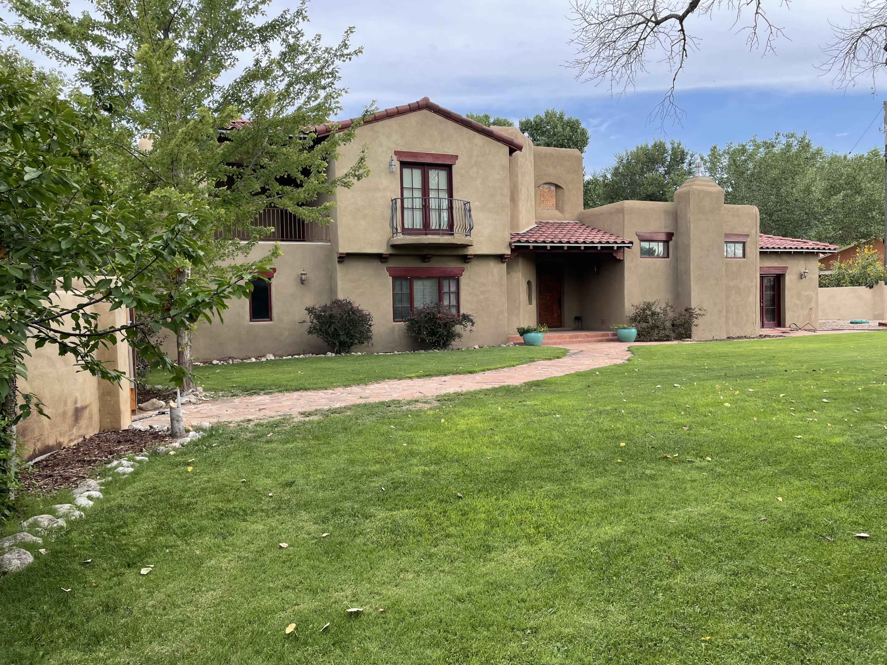 Beautiful Tuscan style home in the green belt of Corrales. Close to tennis courts, Farmers' Market and the Bosque. Lovely bright floor plan with newly remodeled upstairs bath and master shower, new granite countertops in kitchen, custom cabinetry, new stainless cooktop and range hood. Living area adjoining kitchen has gas log kiva fireplace. Lots of possible uses for the upstairs flex space. The front yard resembles a small park with peach, cherry and pear trees along with raised garden beds all on automated sprinkler and/or drip irrigation. Extra large 2 car garage with room for work area and storage. Garage floor has epoxy coating. There is also over 400 sq. ft. of outdoor patio space.
