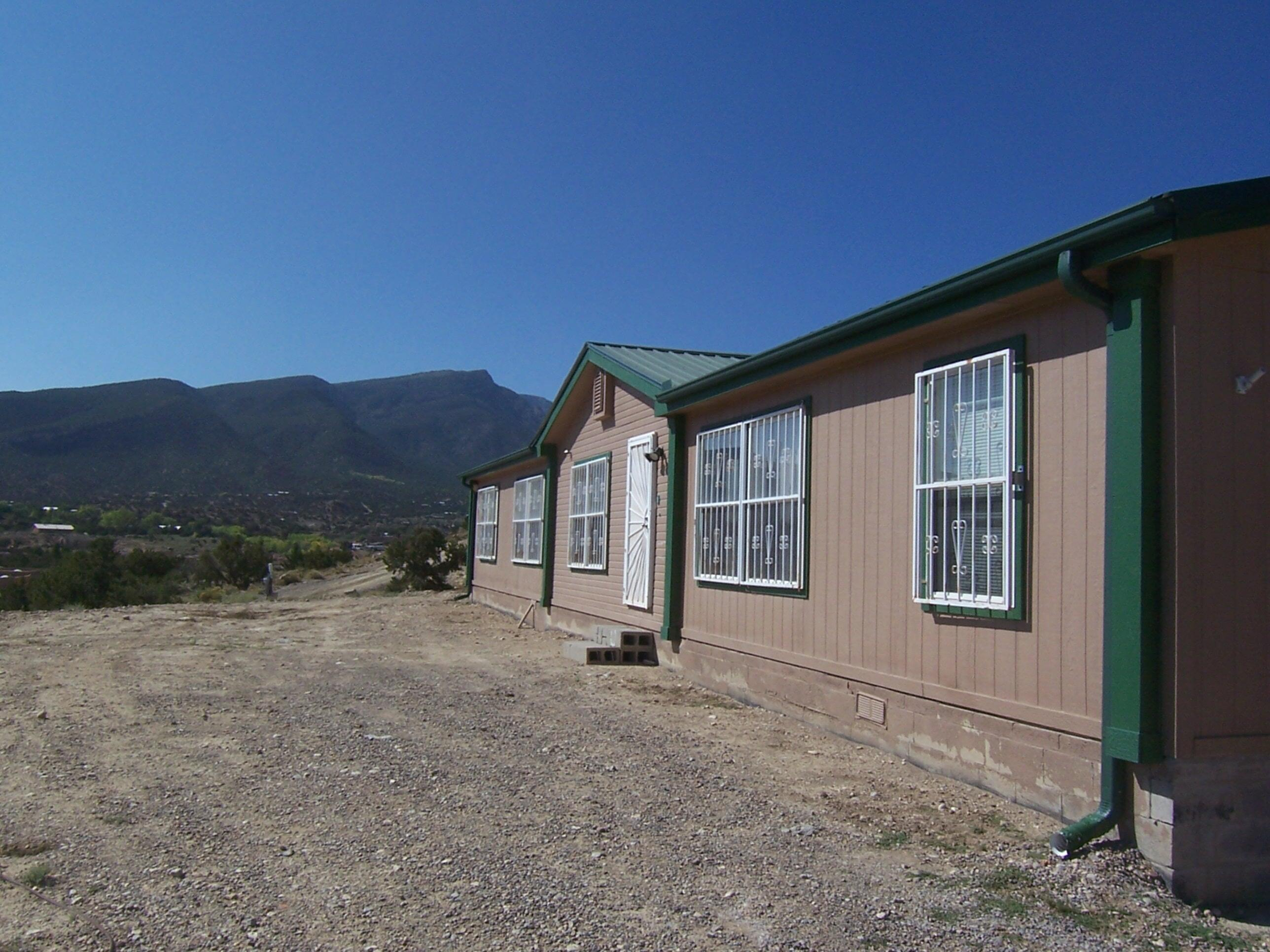 3 BEDROOM + OFFICE ON 1.6 ACRES! $250,000. Affordable 2170 sq ft manufactured home on permanent foundation in Placitas. Just 1/4 mile off paved road with big Sandia views! Great floor plan with spacious separate master suite plus 2 guest bedrooms and office/4th BR. 2.5 baths, living room, family room and dining room! Open floor plan! Master has sitting room, big walk-in closet, double sinks, garden tub and separate shower! Large, open kitchen that was recently remodeled with custom cabinets, beautiful tile floors, raised ceilings! Low maintenance metal roof! 2 storage sheds plus well house. 1 car carport plus plenty of room to add on and for outdoor living. Home is on a 4 lot well share. No HOA, just very minimal covenants.