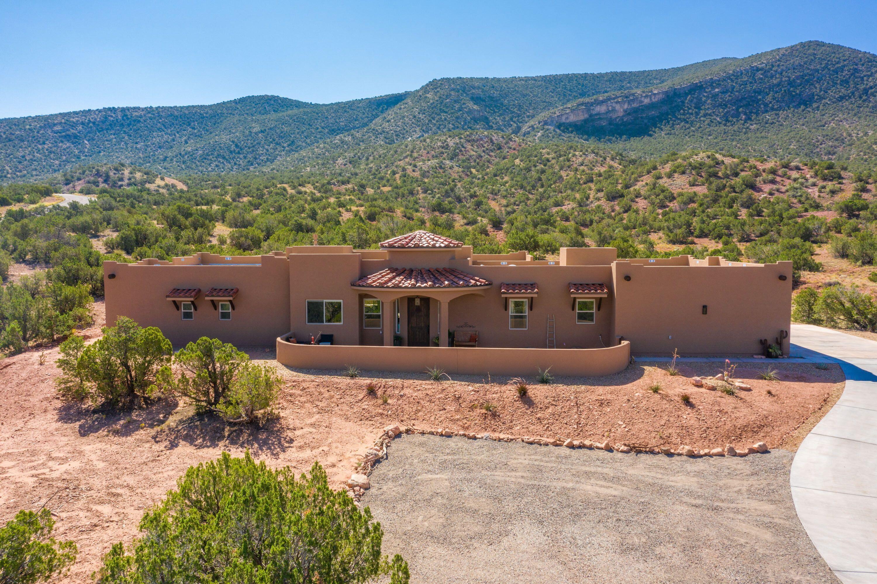 Exquisite Custom Home with Spectacular VIEWS! This stunning impeccable modern day build with old world interior style features an open floor plan, spacious Kitchen open to the expansive Living and Dining rooms. Perfectly situated on 3 Lush Acres to capture Sandia Mountain & Jemez Mountain Views. This custom designed newer home built in 2020 is sure to make an impression. The grand entrance includes an artful hand-blown glass chandelier. Soaring ceilings, wood beams, porcelain tile flooring (no carpet!), custom cabinetry matched throughout the home. Huge windows to take in the views from every room. Kitchen features custom cabinetry, ''leather finish'' granite countertops, large center eat-at island, Frigidaire Cafe series in charcoal matte finish 5 burner gas cooktop & custom vent hood.