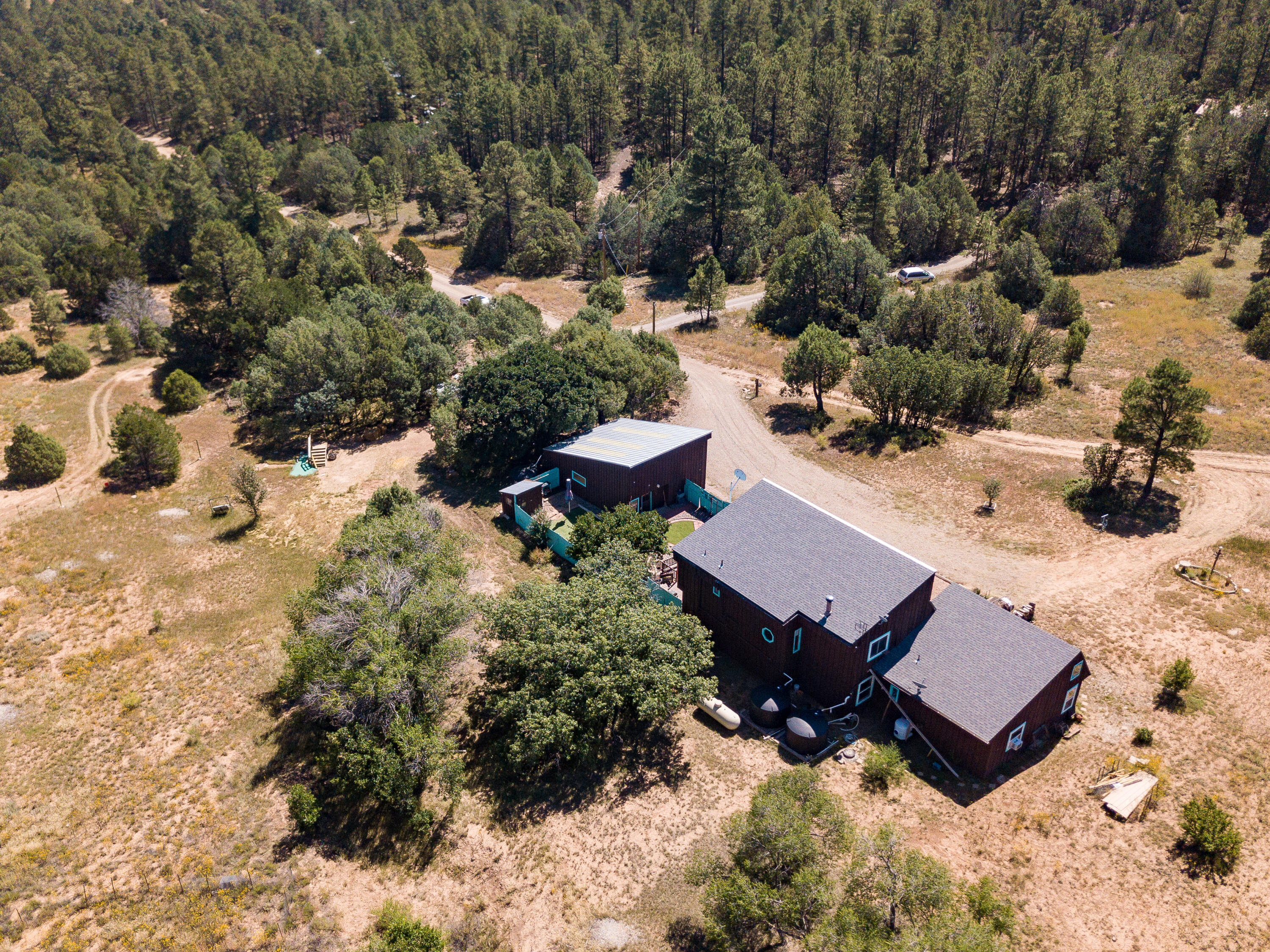 Escape to a private 5 acre estate in the wilderness of Tijeras!  This energy efficient home features solar water heating and a rain capture system for optimum efficiency.   Massive garage and workshop offers plenty of storage for mountain vehicles.  The home as dual master suites, one upstairs and one downstairs giving plenty of options for guests. The wrap around deck overlooks the fenced turf yard and surrounding wilderness.